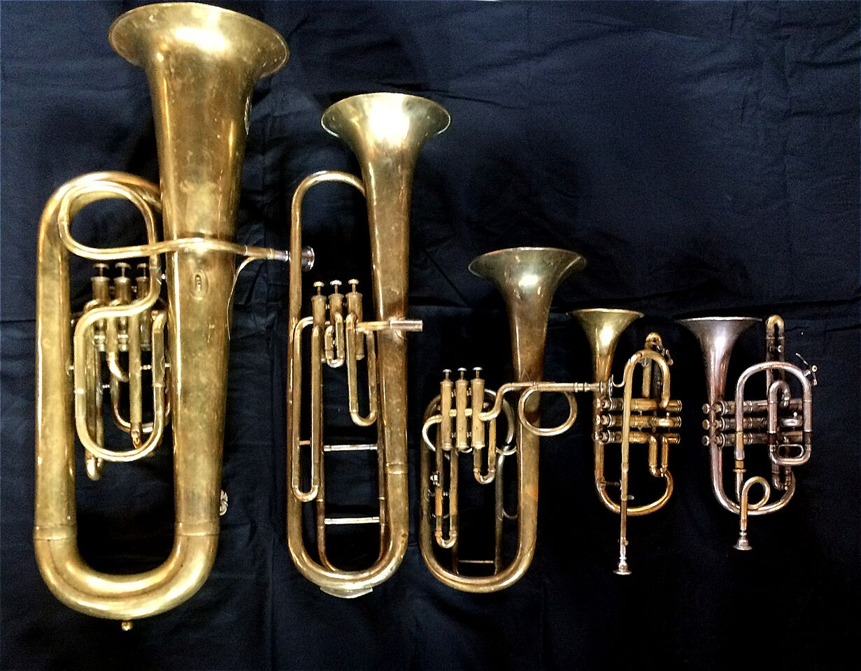 Left to Right:   Contrabass saxhorn in E-flat     by E. Daniel (7167, Marseille, c. 1850),   Baritone saxhorn in C/B flat     by Couturier (Lyon, c. 1865),     Tenor saxhorn in F/E flat/D     by Antoine Courtois (Paris, c. 1855), sold by Arthur Chappell (London)  ,   Cornet in E-flat by Couesnon     (94 Rue D'angouleme Exposition Universelle De Paris 1900),      Cornet in C/B-flat     by Henry Distin New American Model (9580, Williamsport, PA, c. 1895).