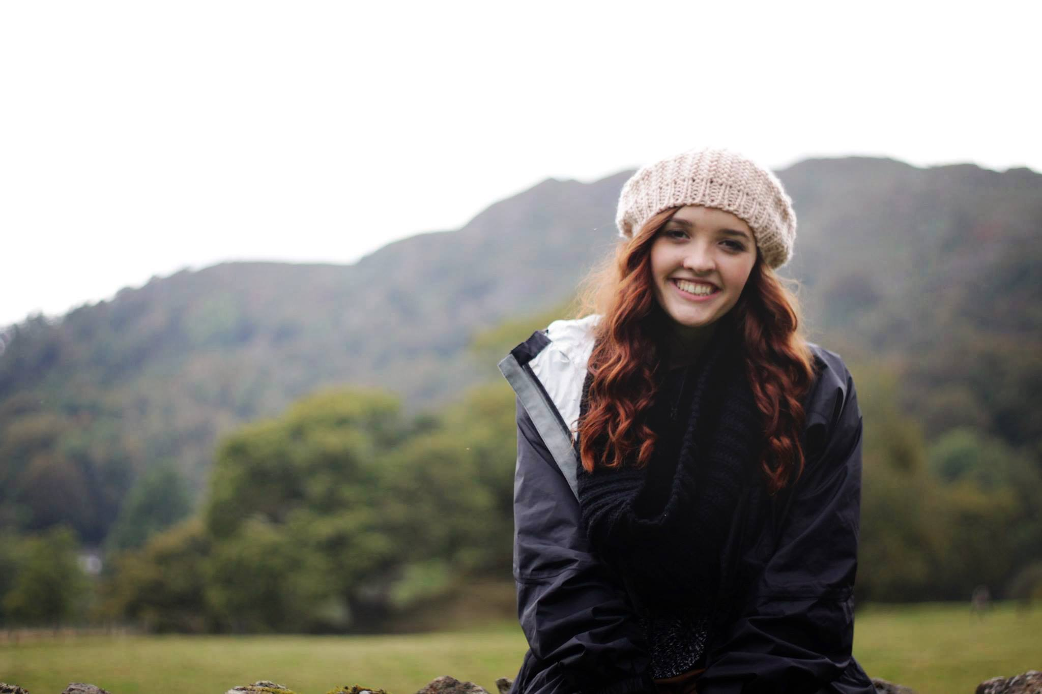 girl in lake district in hat smiling for camera look for the light photo video celine reese