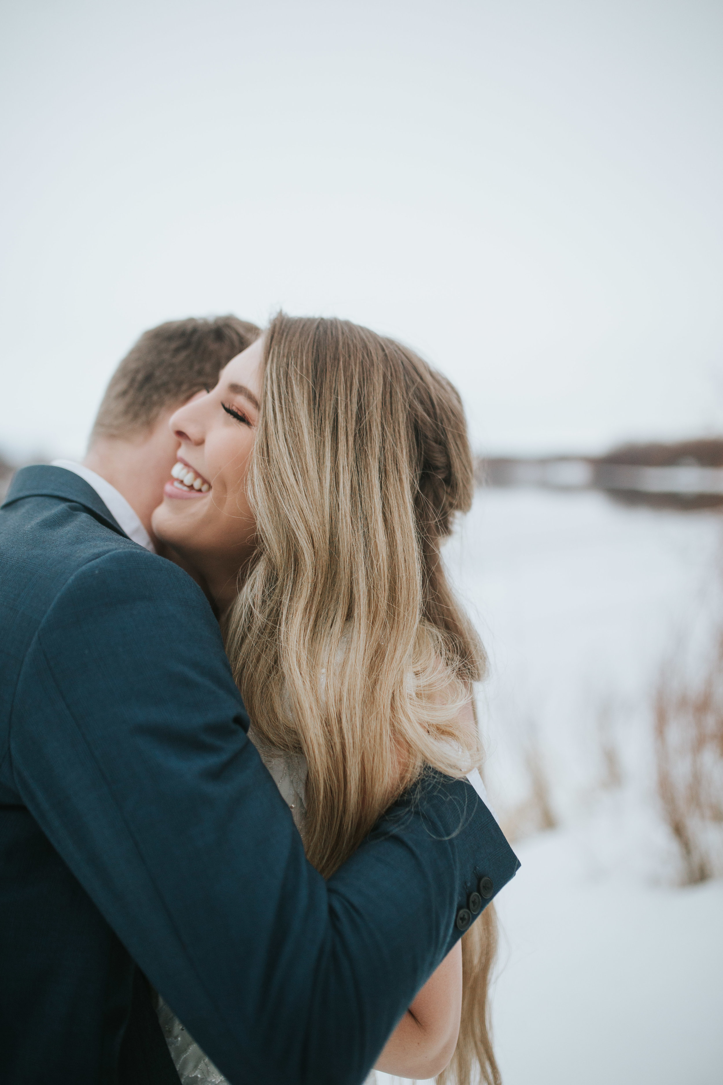 couple hugging in snow bridal session wedding dress rexburg idaho wedding photographer