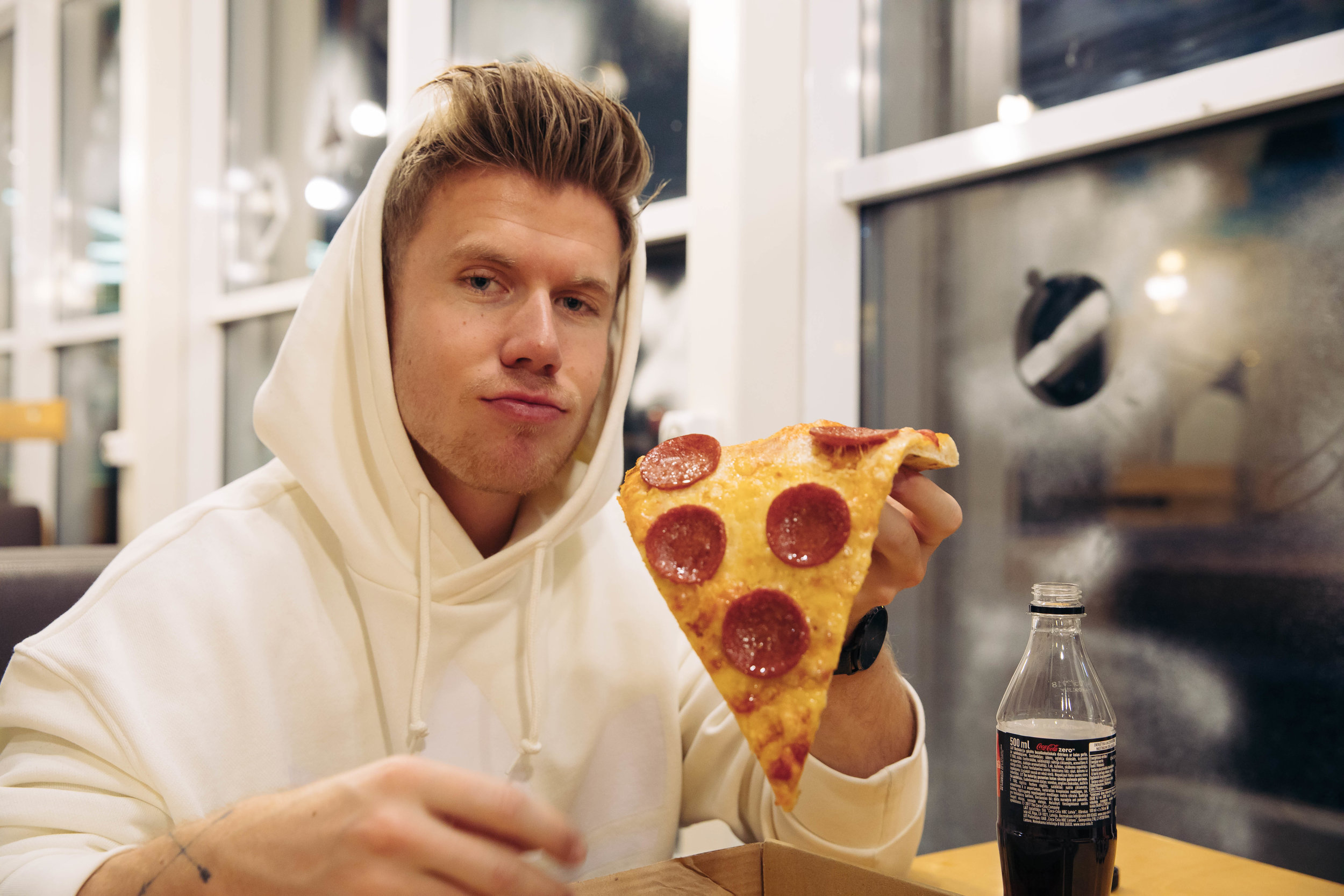 Kim Sørensen eating pizza at a restaurant in Riga.