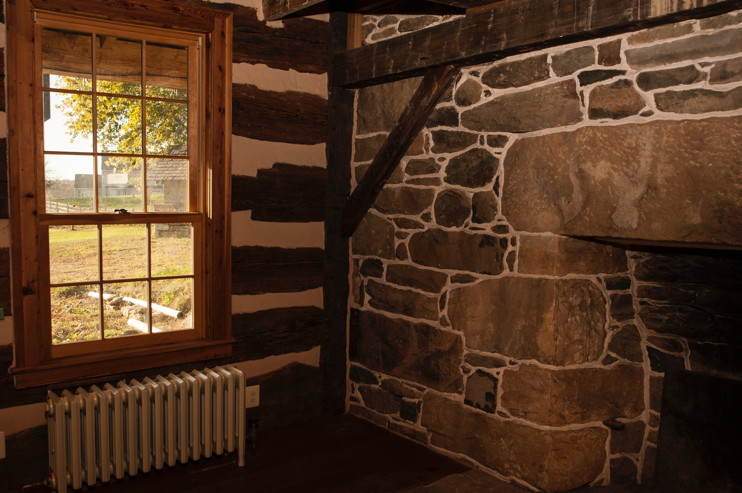 In the log house addition, new windows are set into reclaimed wood frames.