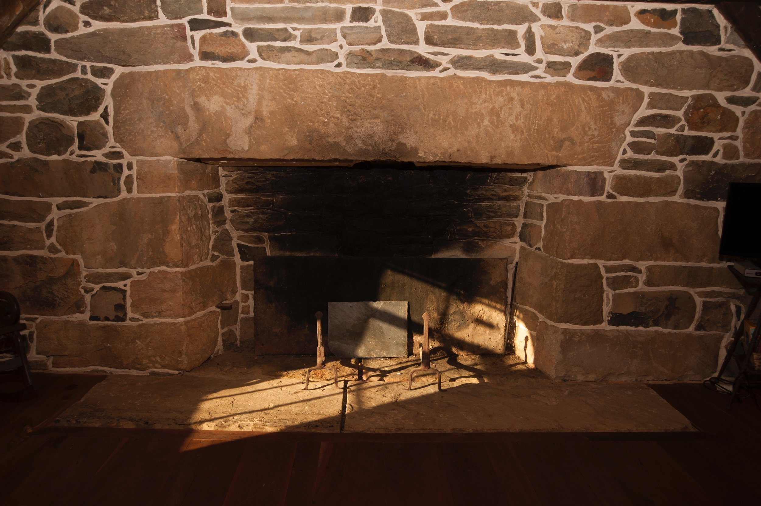 """The massive stone fireplace is set into the thick """"ender."""" wall."""