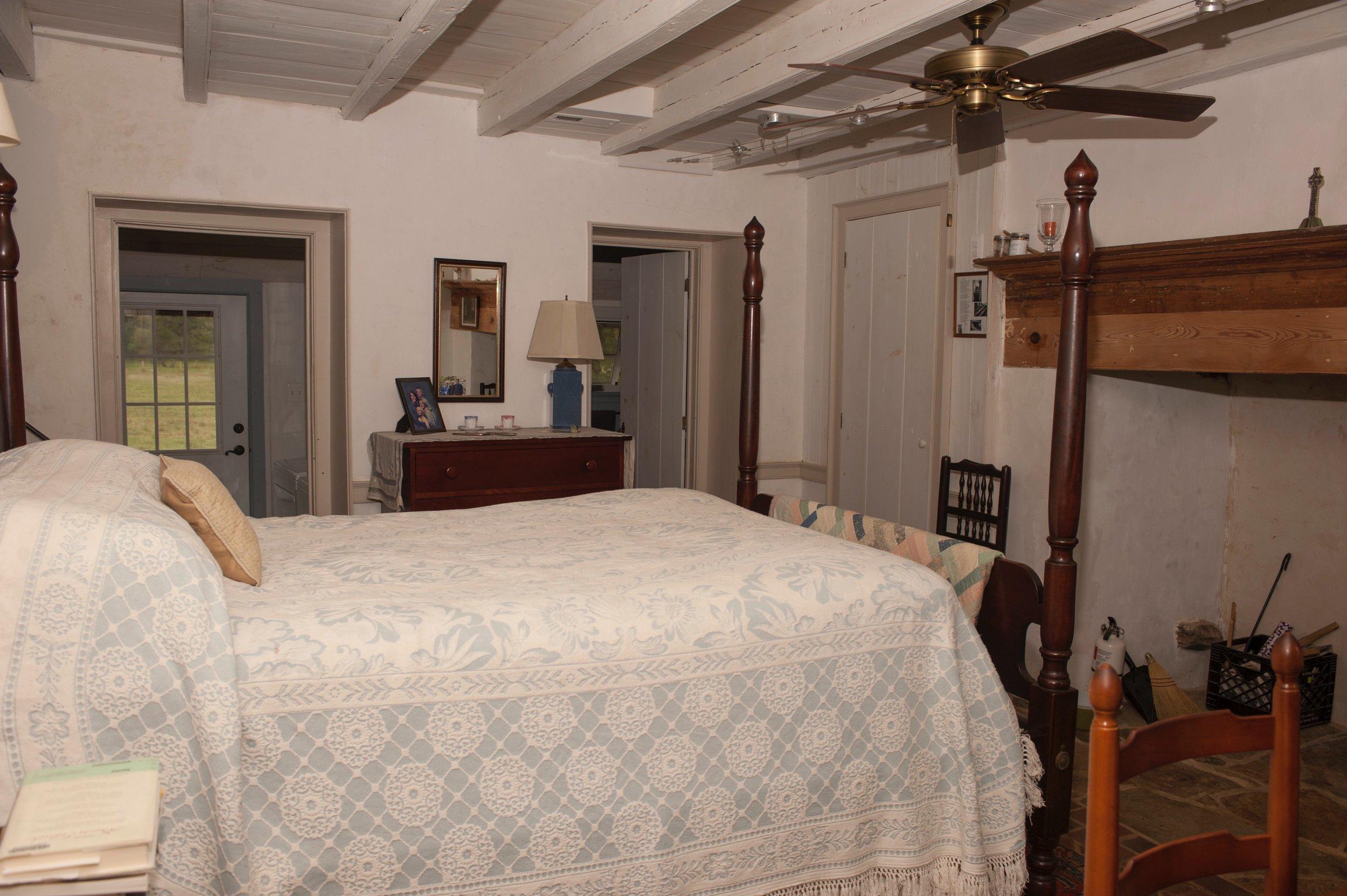 Master bedroom features restored beams and radiant-heat brick floor.