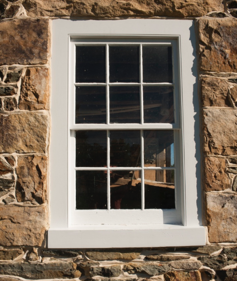 Close-up of window featuring new Marvin window set into custom frame of old wood.