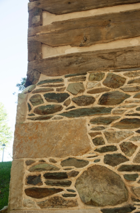 Corner stonework supports the structures logs, all notched at the corners.
