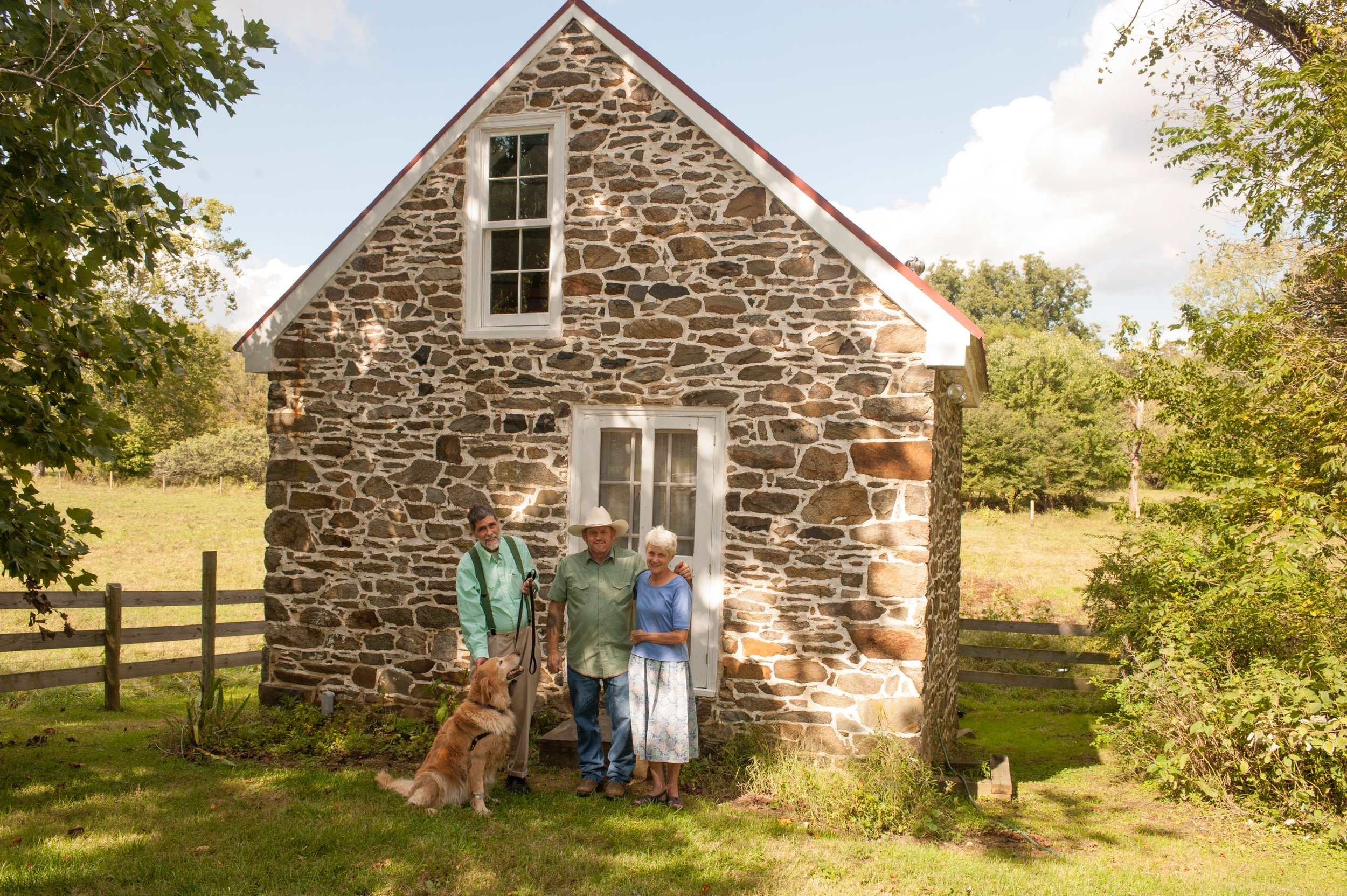 Gail and Perry Epes with their dog, Jacob, and Allen Cochran, who restored the masonry and renovated the interior of the original spring house into a small and delightfully livable space.