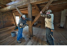 Mike Shockey and Joe Reidel place a timber support beam in an old bank barn that's being restored north of Hamilton. (Photo by Douglas Graham/Loudoun Now)