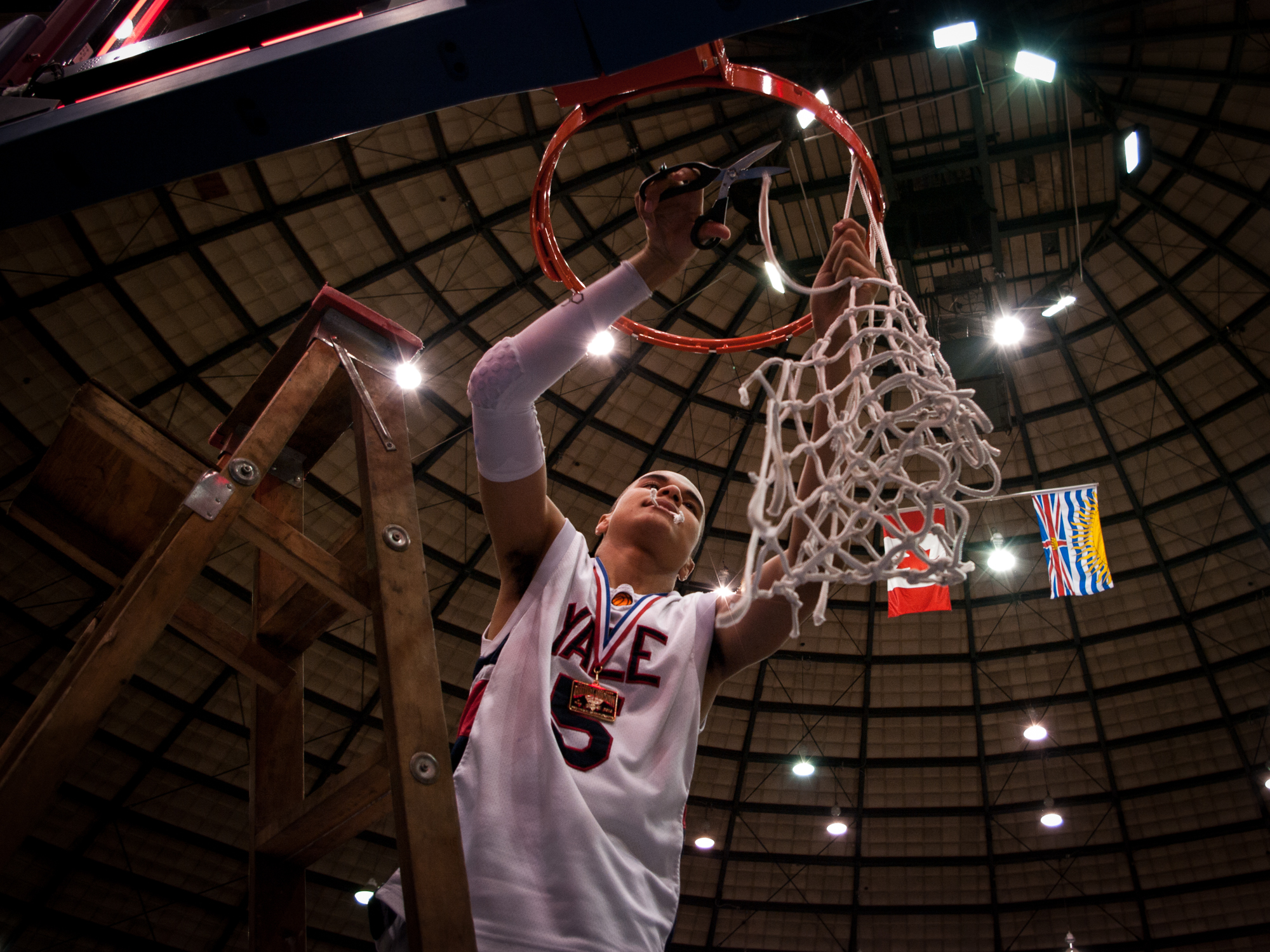 Jordan Blackman cuts down the net after his team won the 2010 BC High School Basketball Championships.