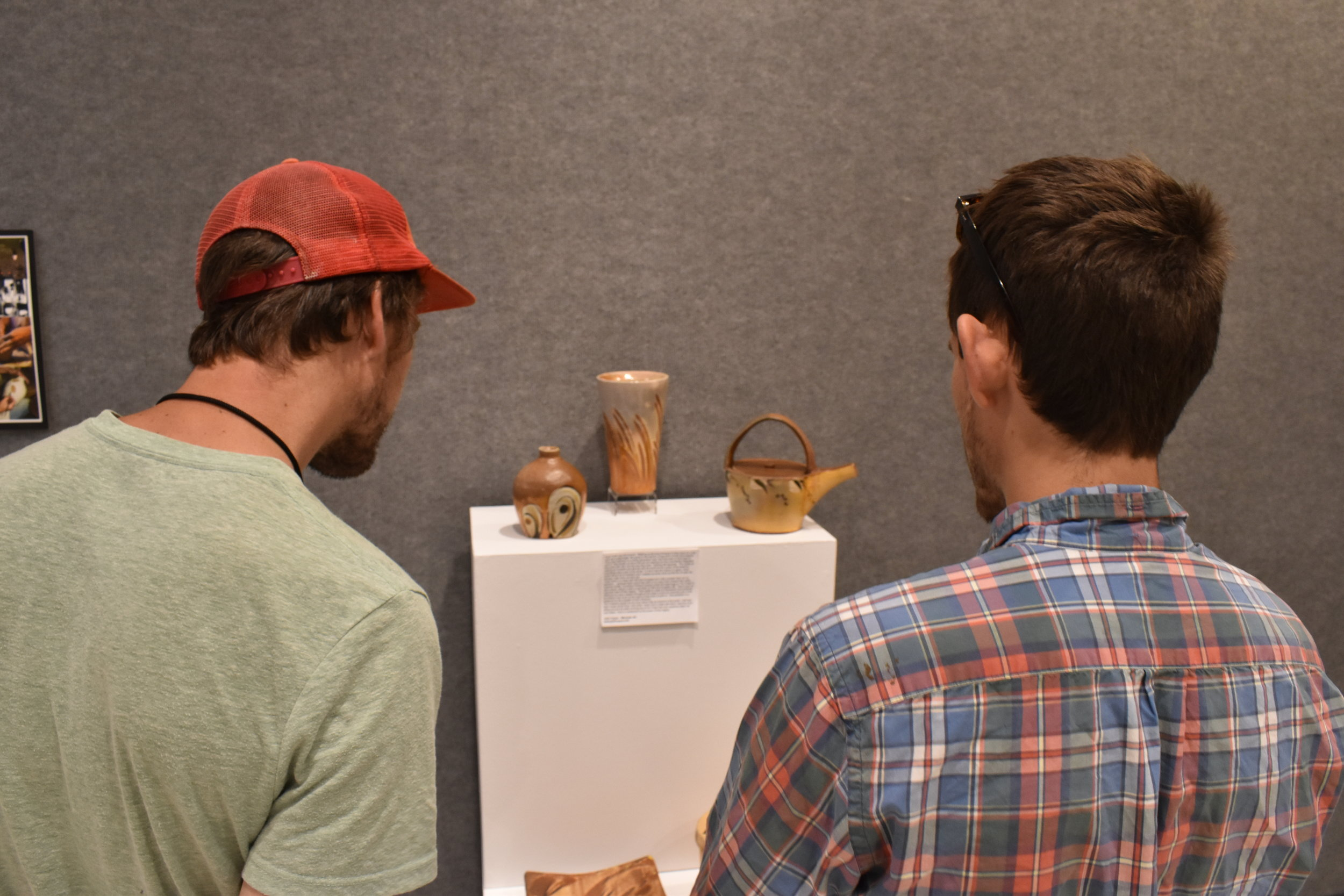 Tom Alward & Hamish Jackson observing a group of pots. The vase in the center of the pedestal was made by Josh Copus, and the pots around it are Rock Creek pots from his personal collection.