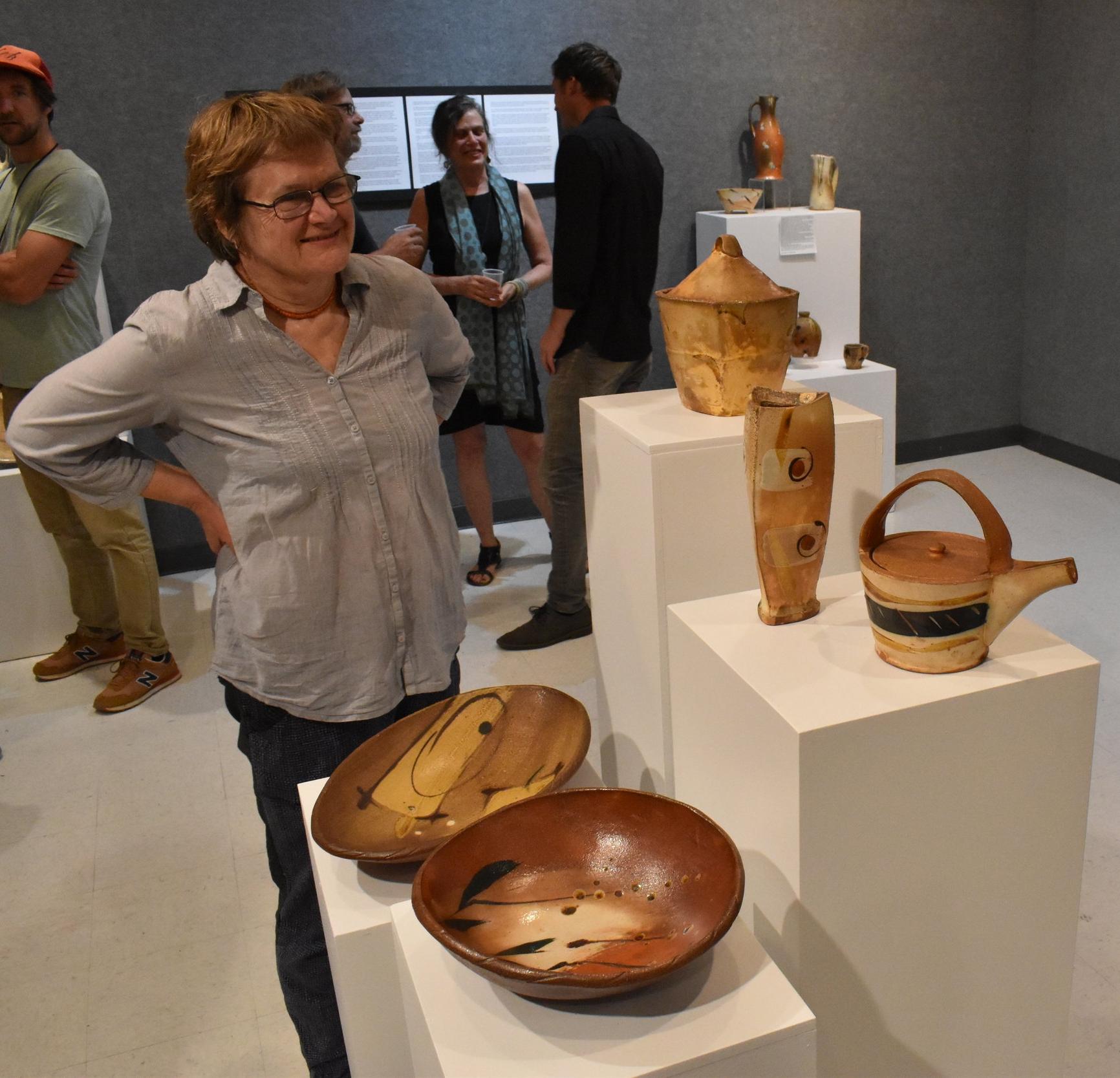 Australian potter Sandy Lockwood, observing the pots.