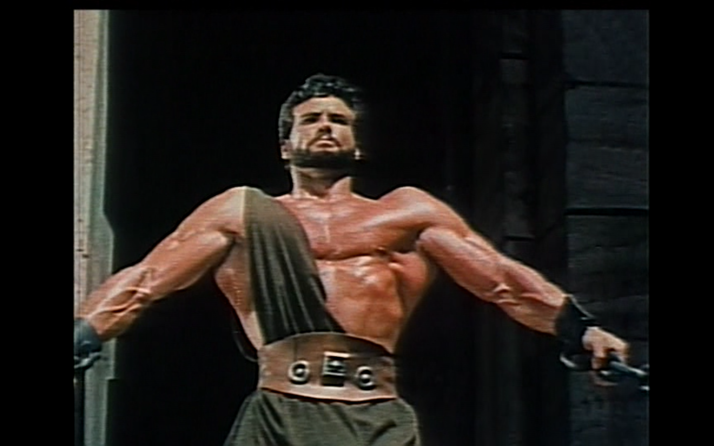 """Figure 4: Hercules (Steve Reeves) pulls down a temple at the conclusion of  Hercules  (Francisci 1958). The look of Reeves' character (minus the """"H"""" symbol on his weight-lifting belt) probably inspired the look of Marvel's Herc. Image credit: screen capture (Embassy Pictures/Galatea Film)."""