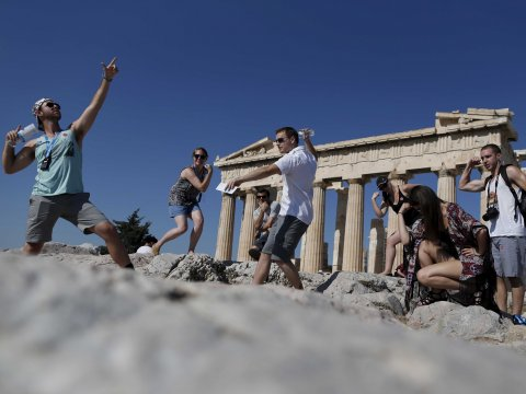 Figure 1: Tourists take a photo with the Parthenon as backdrop, striking poses reminiscent of ancient Greek statuary. Image credit:   ekathimerini.com.