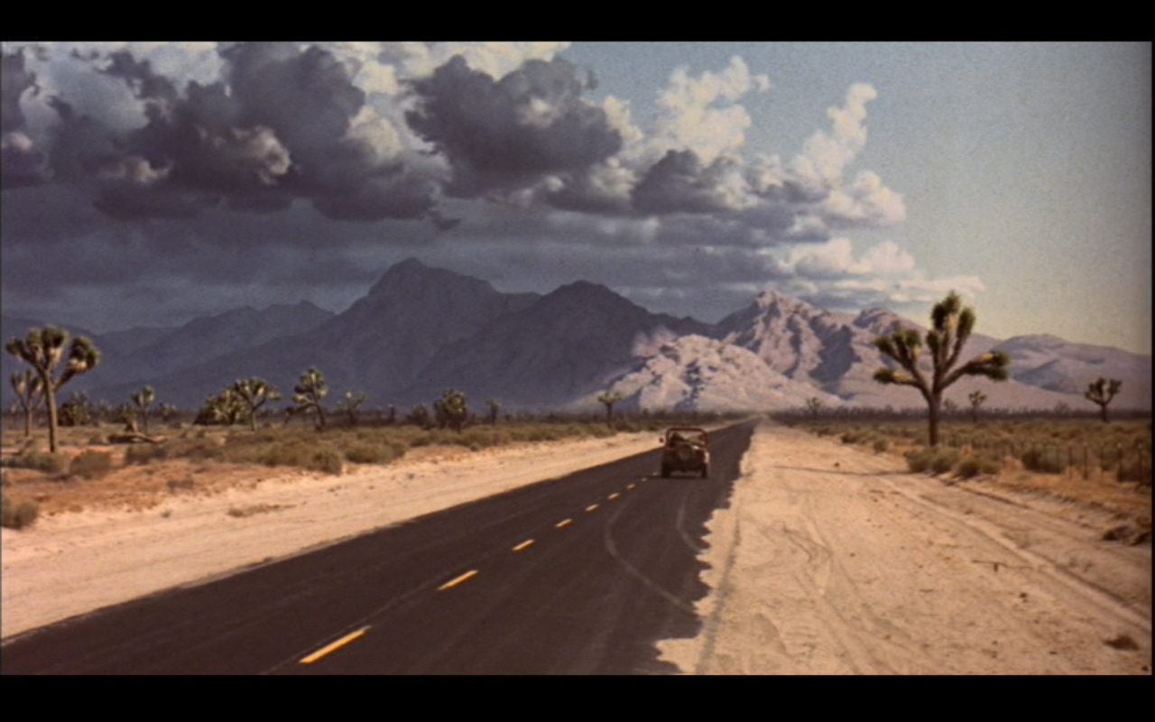 """Figure 1: this is the last shot of  T1 . Sarah faces an unknown future, mirrored in the clouds that cover the sun in the left half of the shot and the brilliant sunshine on the right. The starkness and brutality of the desert environment also reflect the mood. """"He says a storm's coming."""" """"I know."""""""