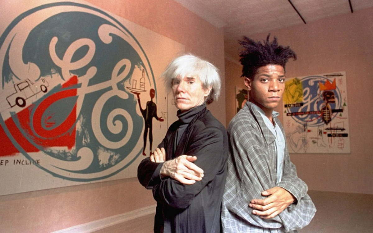 Figure 3: Andy Warhol and Jean-Michel Basquiat pose in front of a gallery showcasing their work.