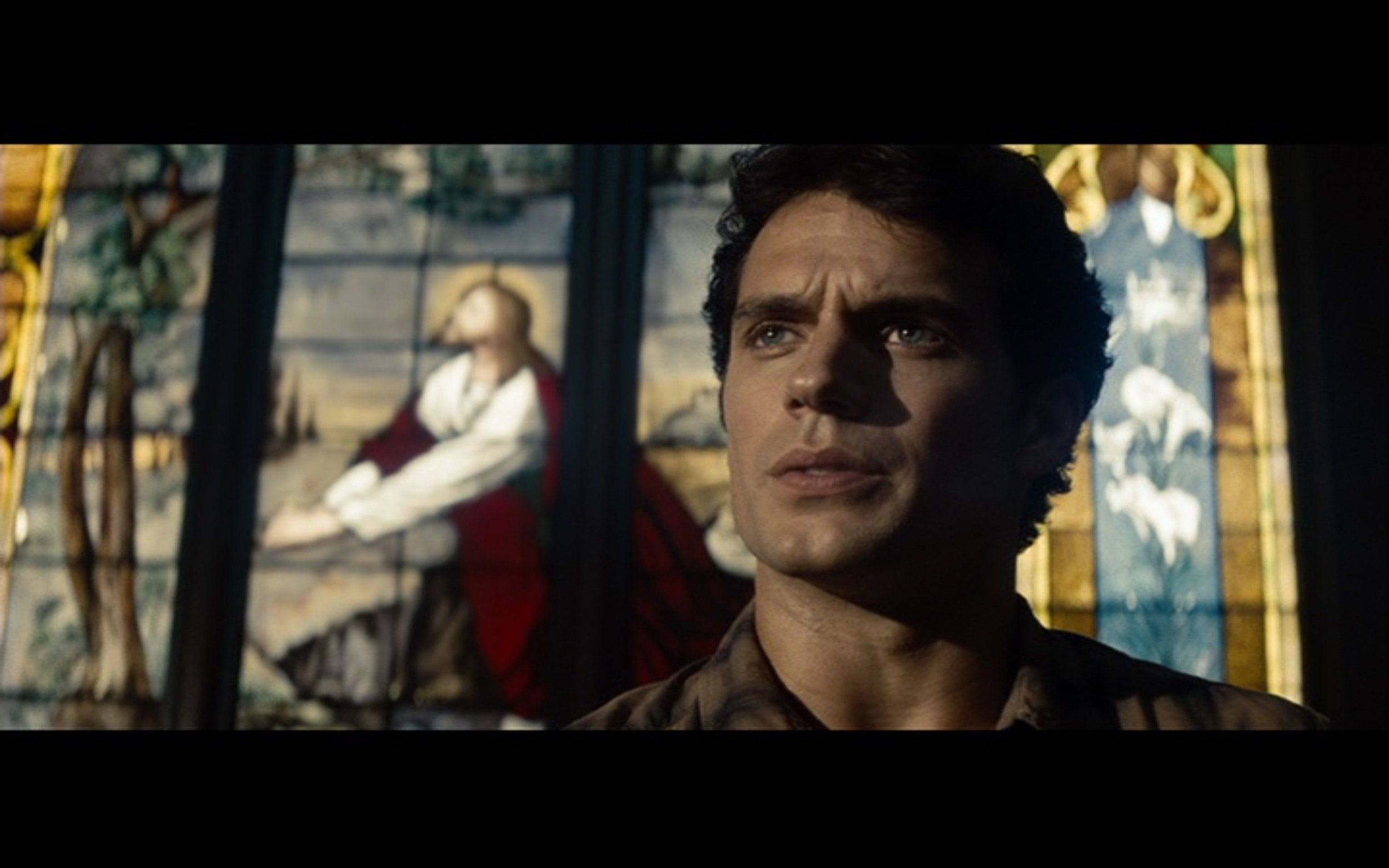 Figure 3: This shot from  Man of Steel  aligns Clark's face with a praying Jesus of Nazareth depicted on a stained-glass window.  Man of Steel  (Snyder 2013), DC Entertainment/Legendary Pictures/Syncope/Warner Bros. Pictures.