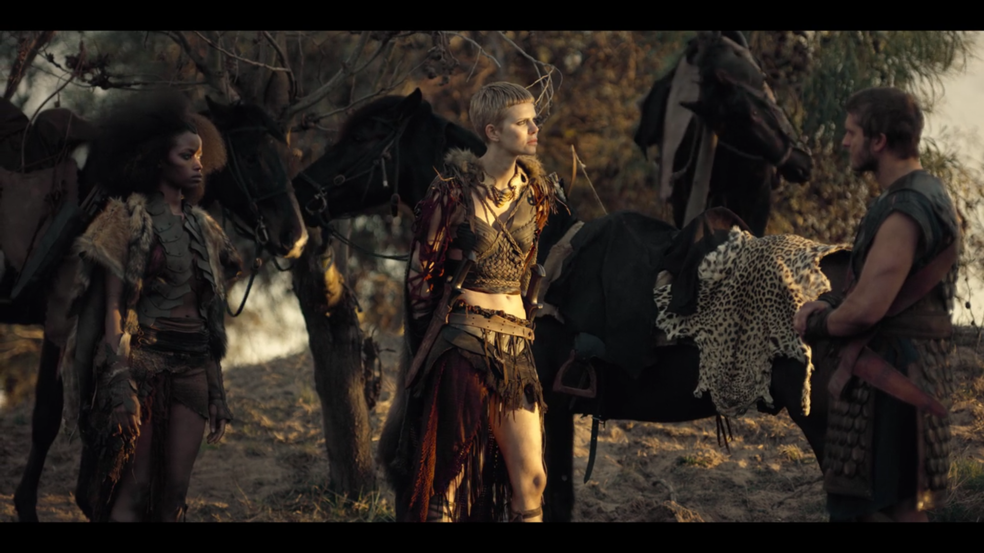 """Figure 1: Paris (right) converses with the Amazon queen Penthesilea (left) while her lieutenant Ainia looks on in the episode """"Battle on the Beach."""" The difference between the Trojan prince and the women warriors is made clear visually by the animal skins that both Amazons wear and use as padding on their mounts, as compared to the tooled leather of Paris' garb. Credit: BBC/Netflix."""