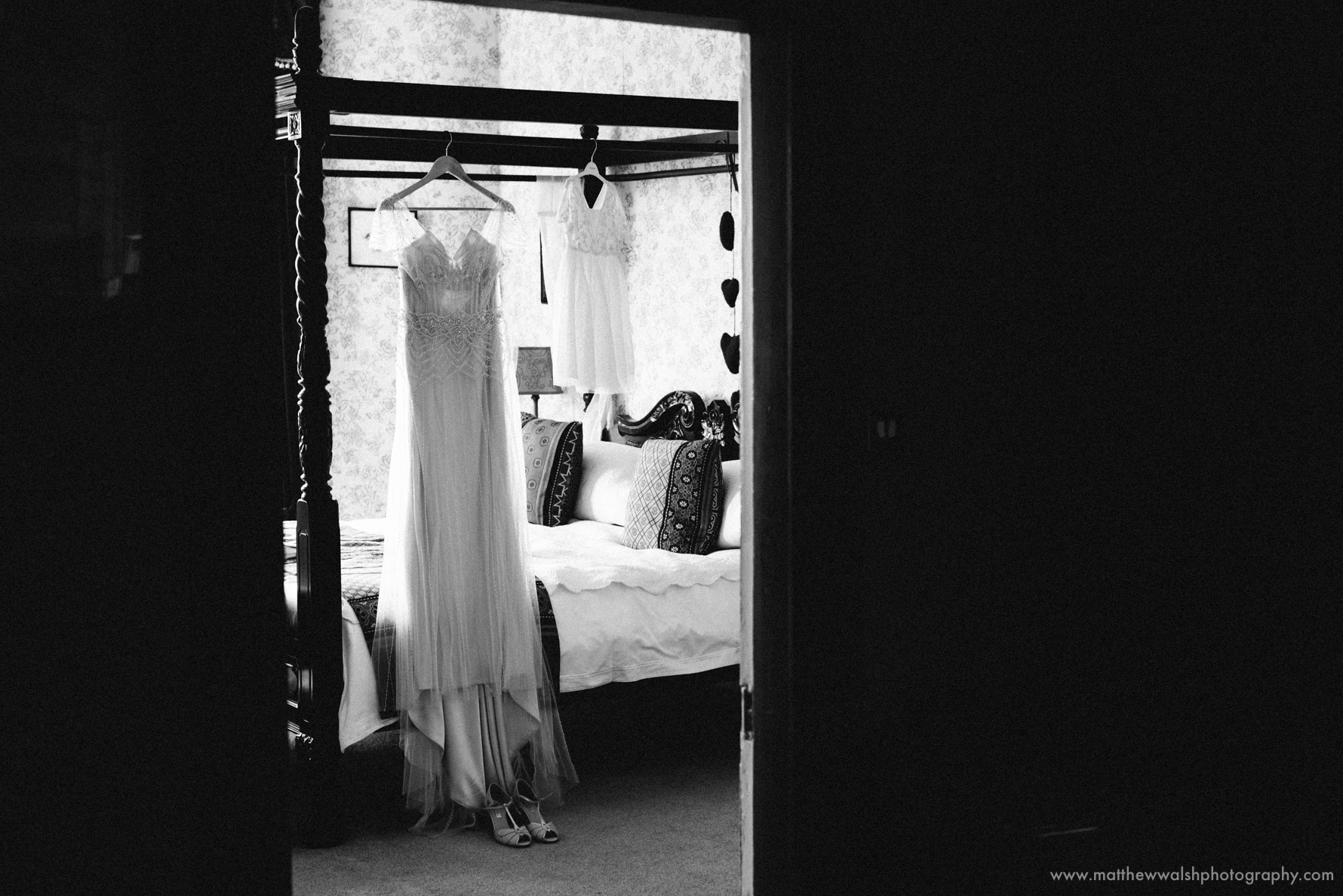 Wedding dress hanging from the four post bed in the bridal suite