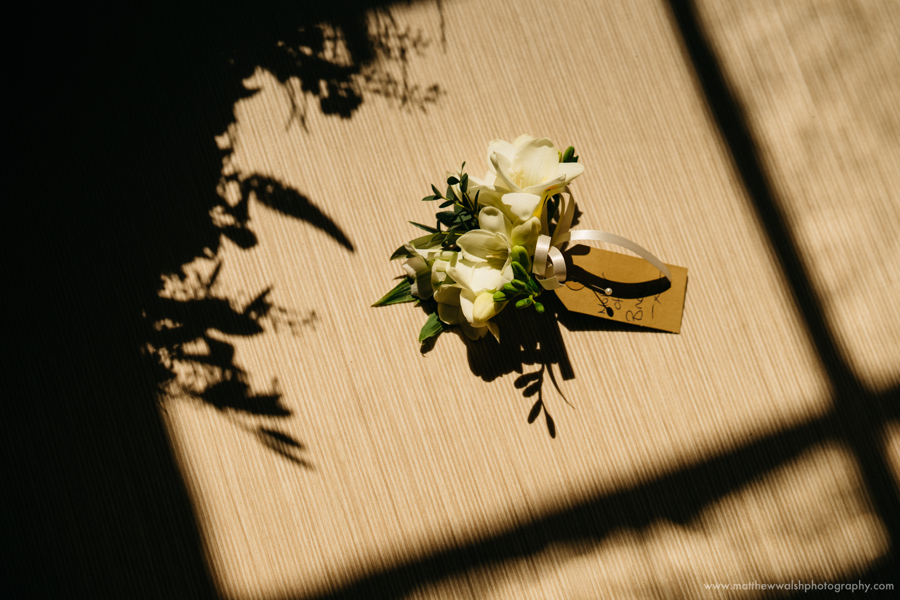 Mother of the brides button hole flowers lay in a pocket of sunlight