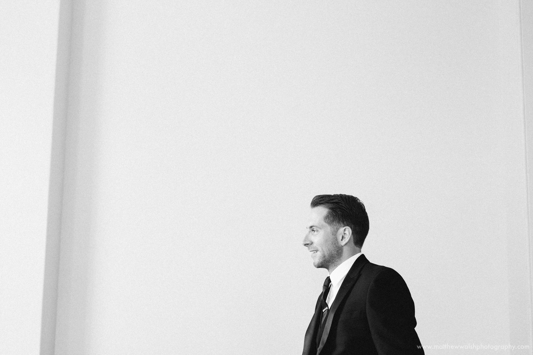 Groom standing against a white wall in one of the grand rooms, natural light flooding through the window