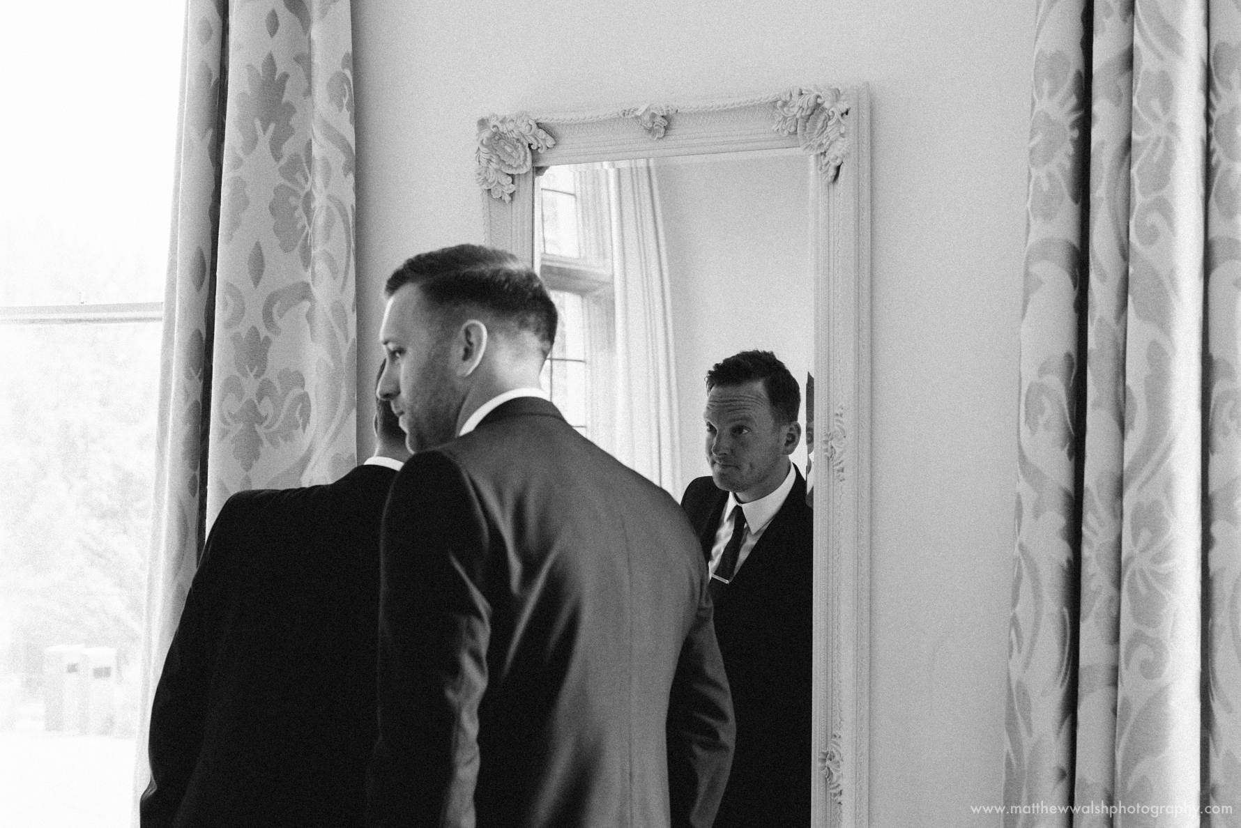 Best man and best man check themselves in the mirror