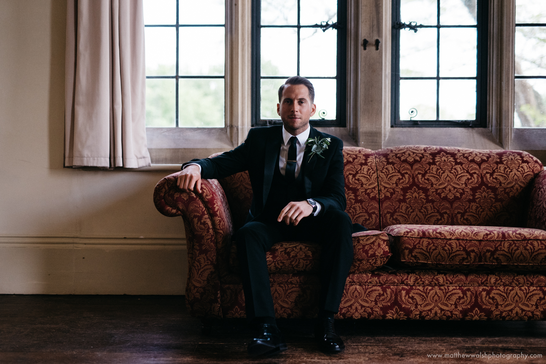 Groom sitting for a portrait before the ceremony