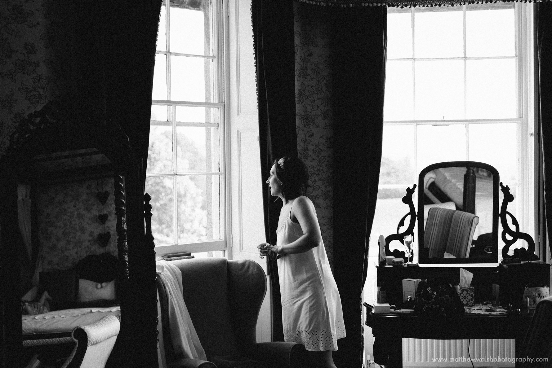 Bride looking out of the window as guests start to arrive down below
