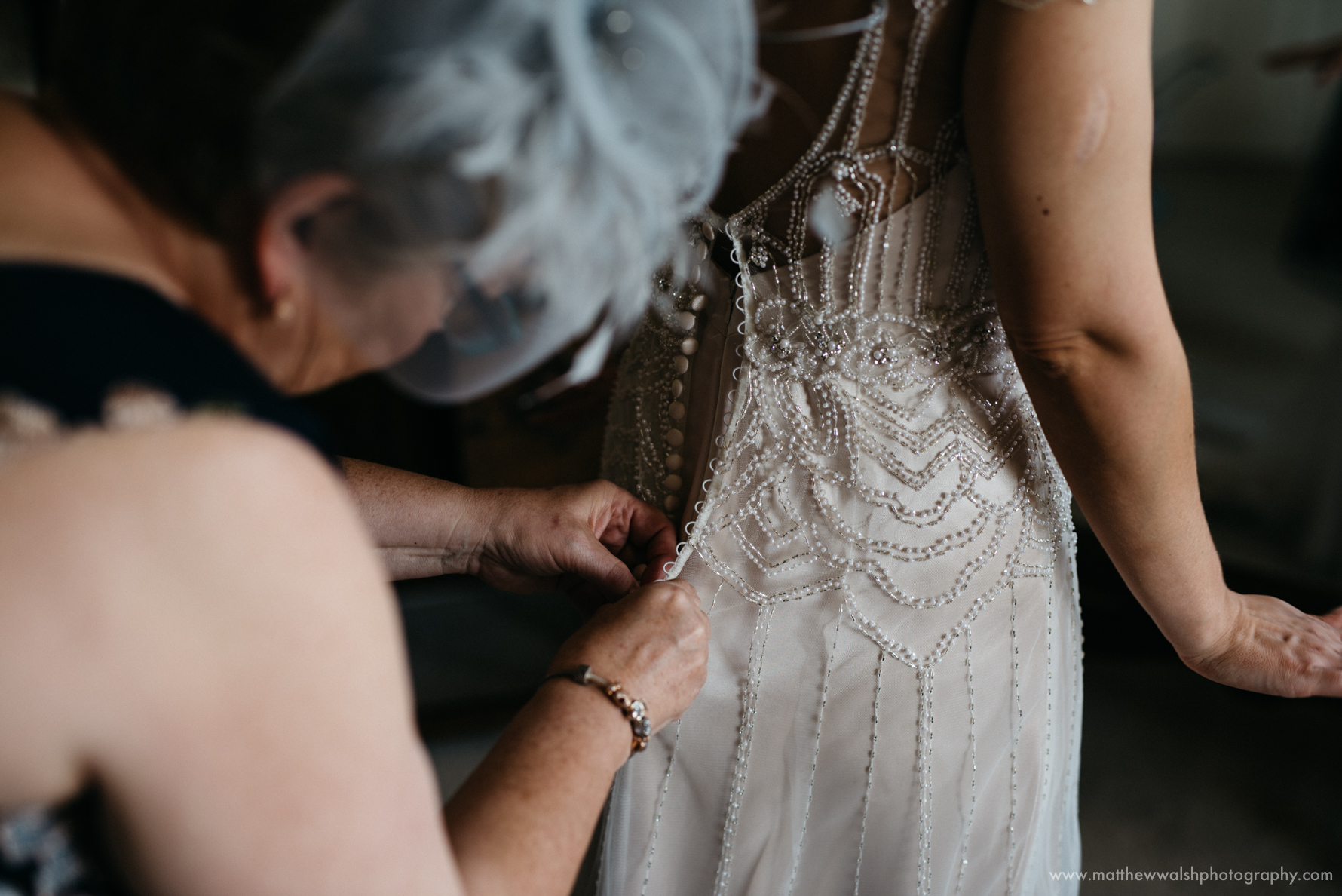 Mother of the bride traditionally fastens the buttons of the brides dress