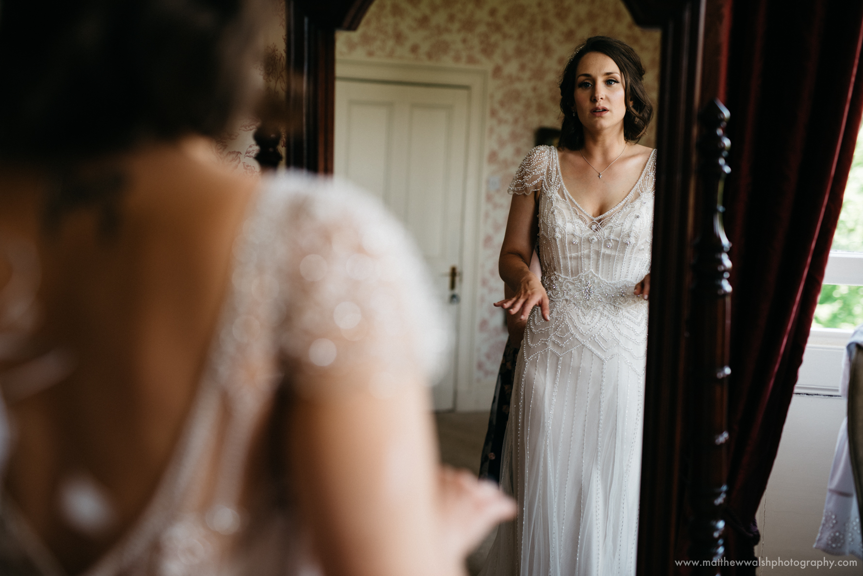 Bride looks in the mirror with her elegant wedding dress on looking a little nervous