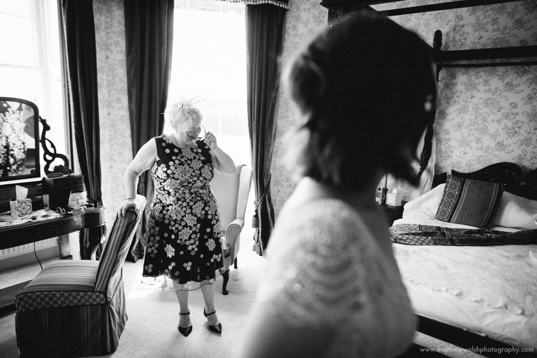 Mother of the bride watches her daughter in the bridal suite