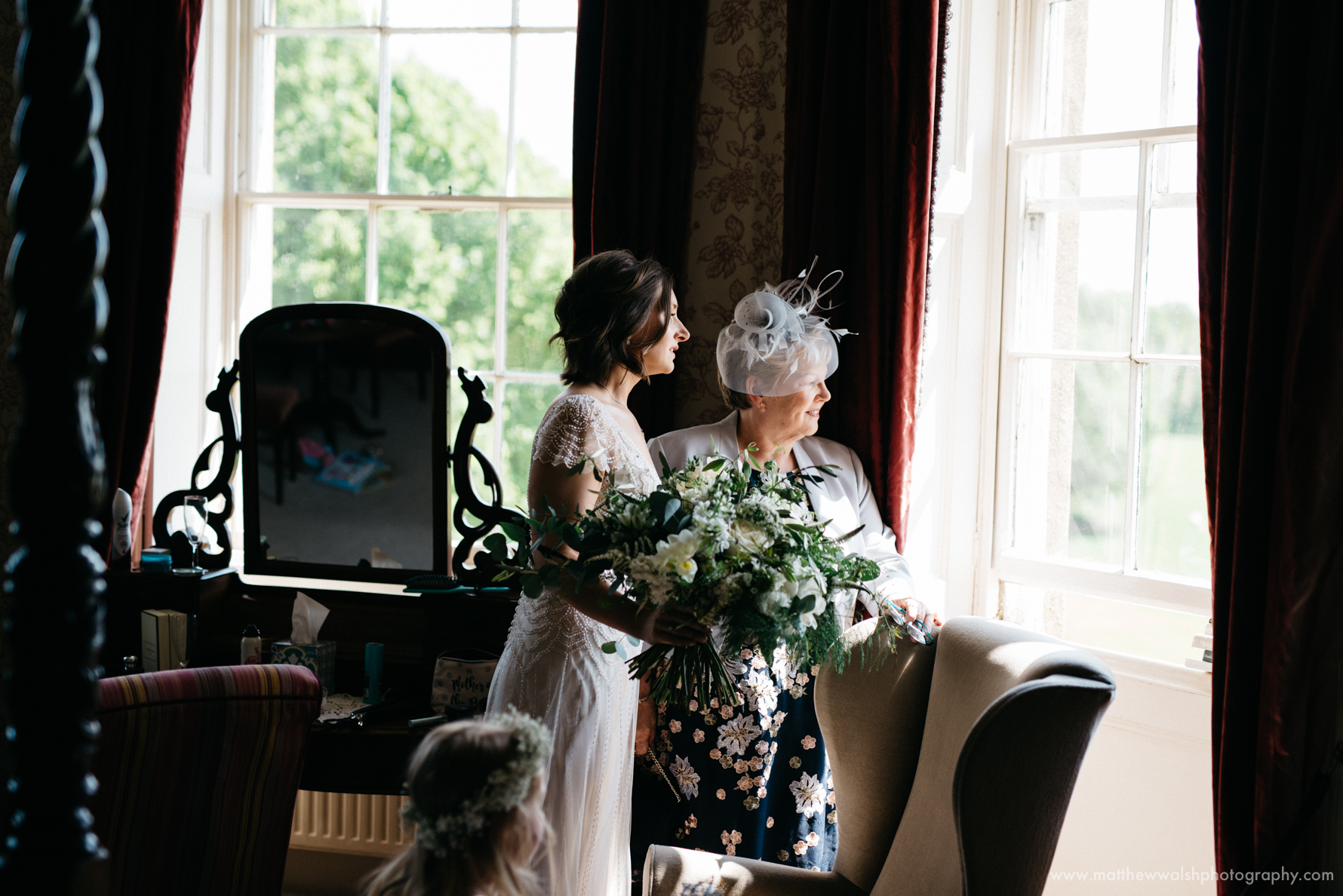 Bride and mum look out of the natural light window to see the guests arriving