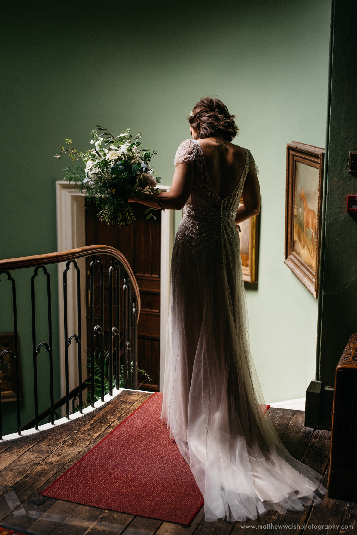 Bride at the top of the stairs at Burton Court as thew waits for her father to lead he down, perfect window light is a photographers dream