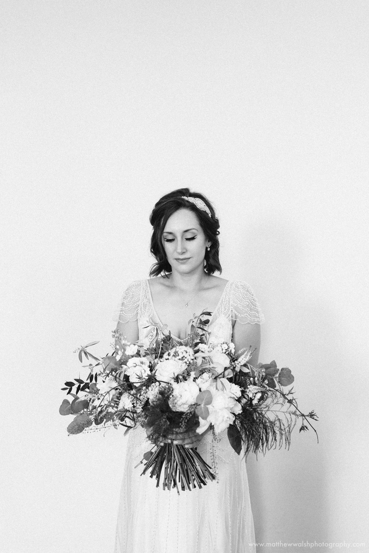 Bride against white wall black and white photo