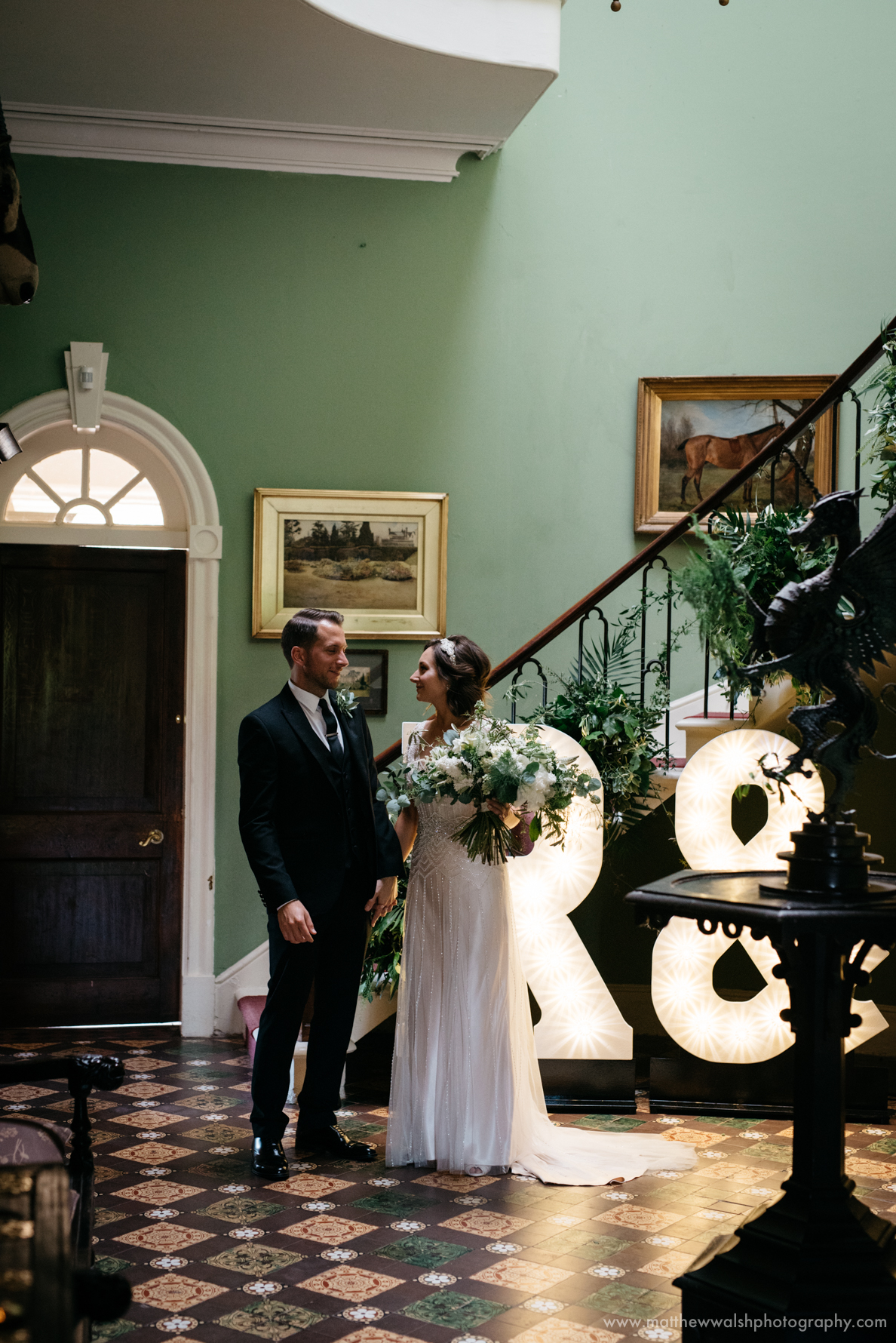 Bride and groom in the hallway by the letter lights