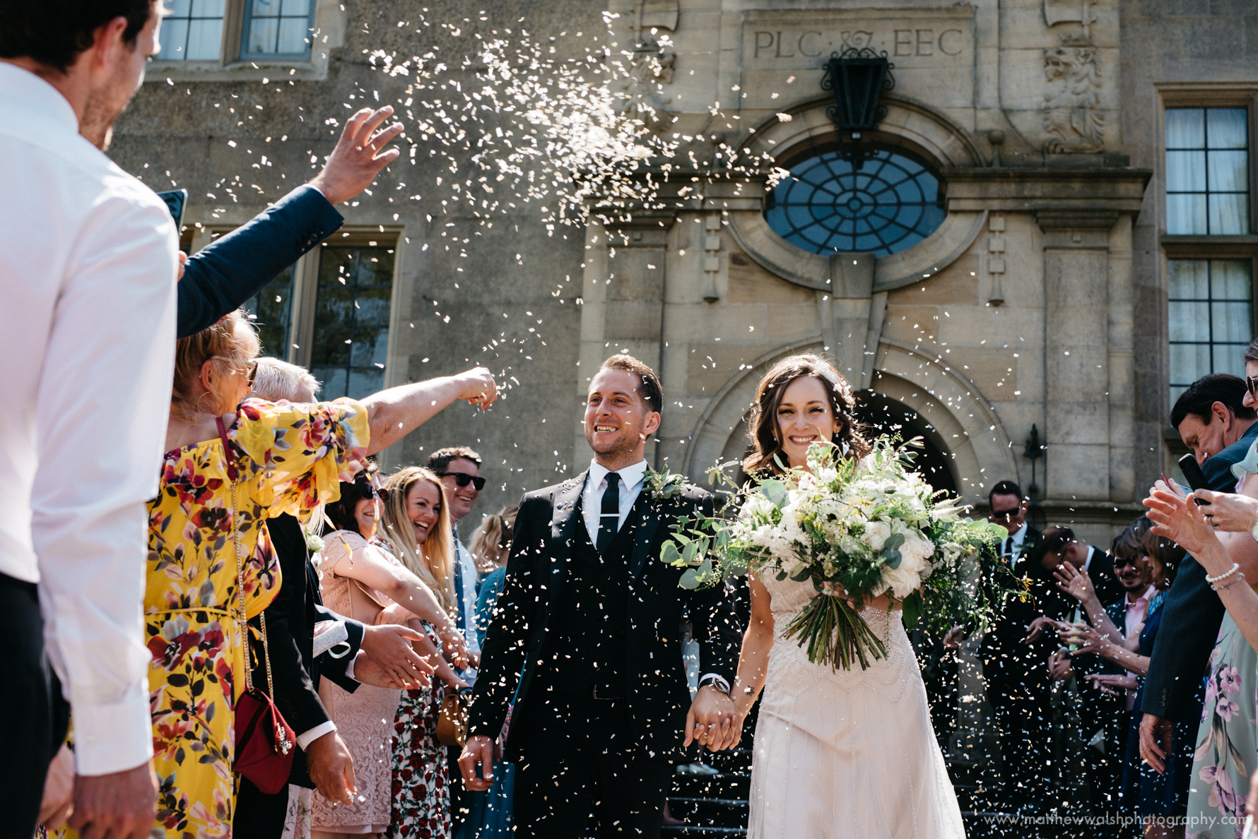 A captured moment at Burton Court as the bride and groom are showered with Confetti