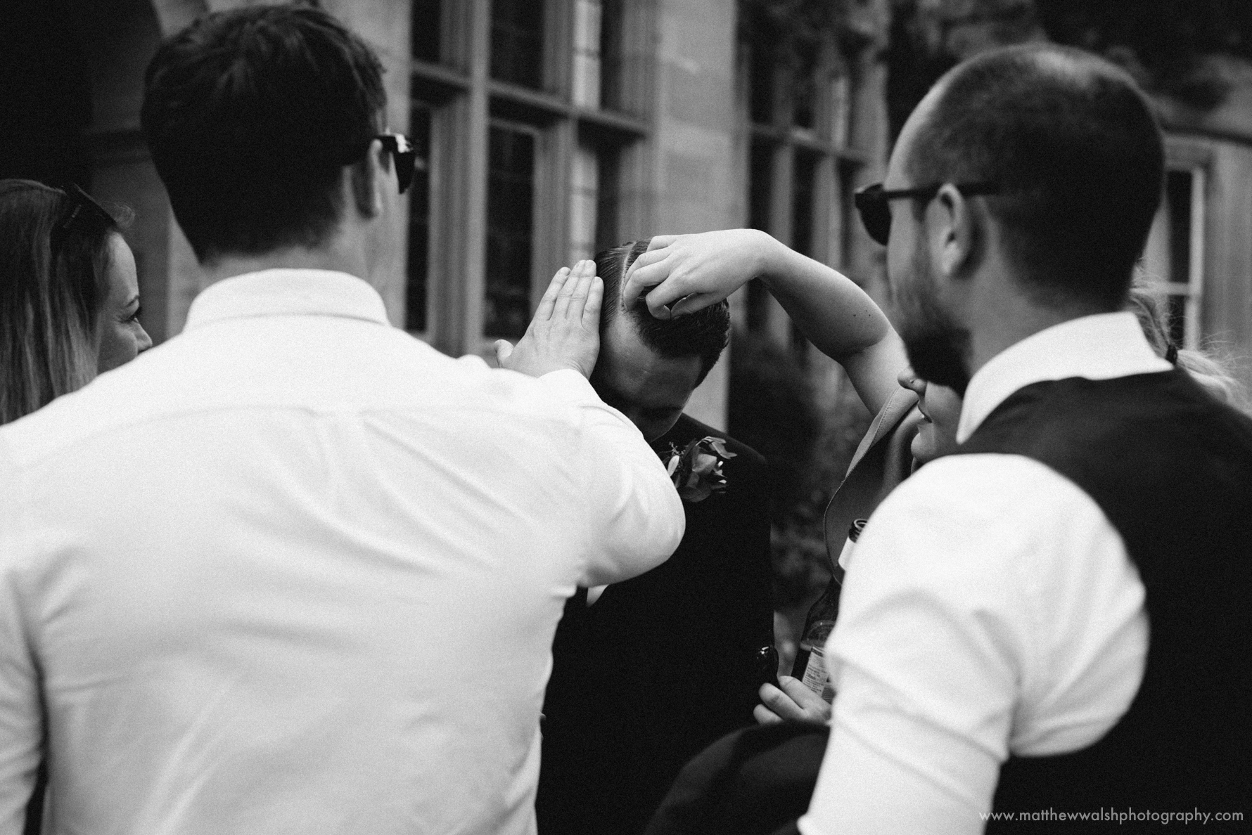 Friends remove confetti from the grooms hair