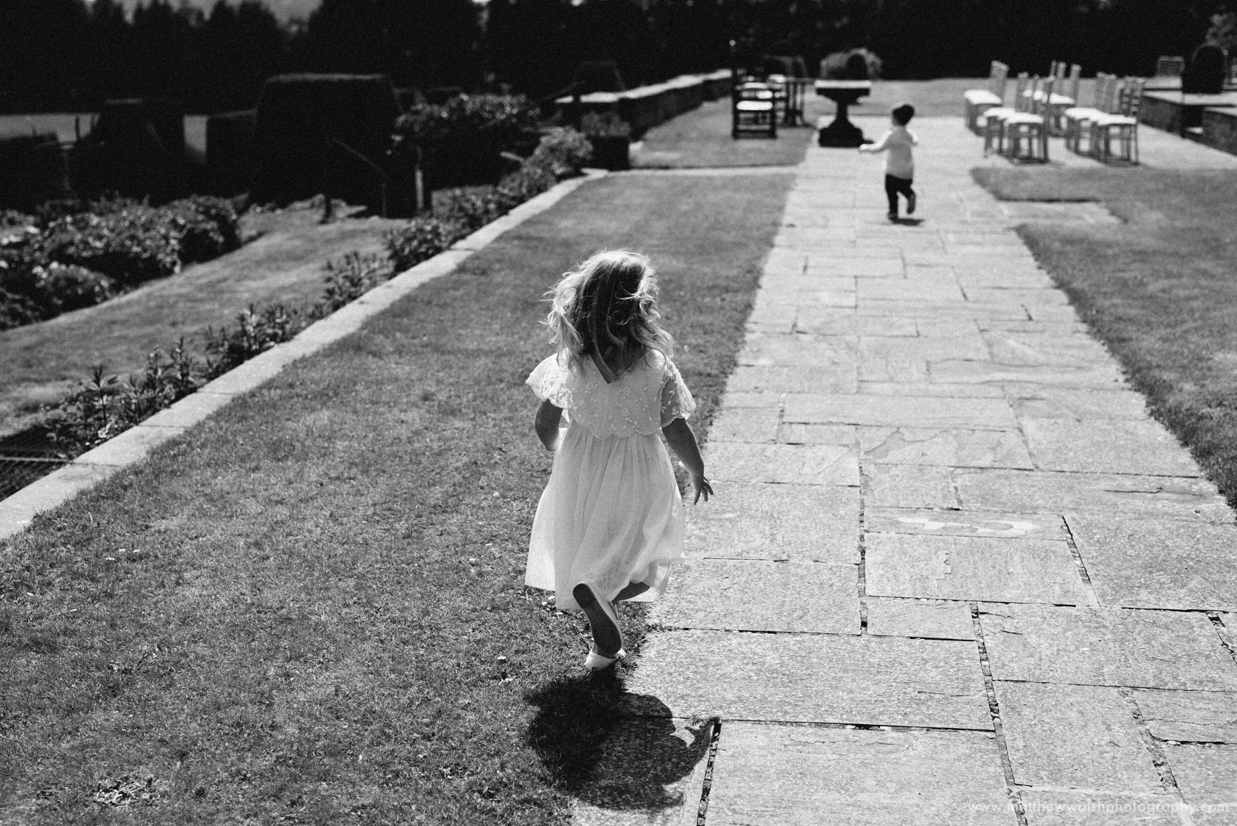 Flower girl runs on the grass in the gardens