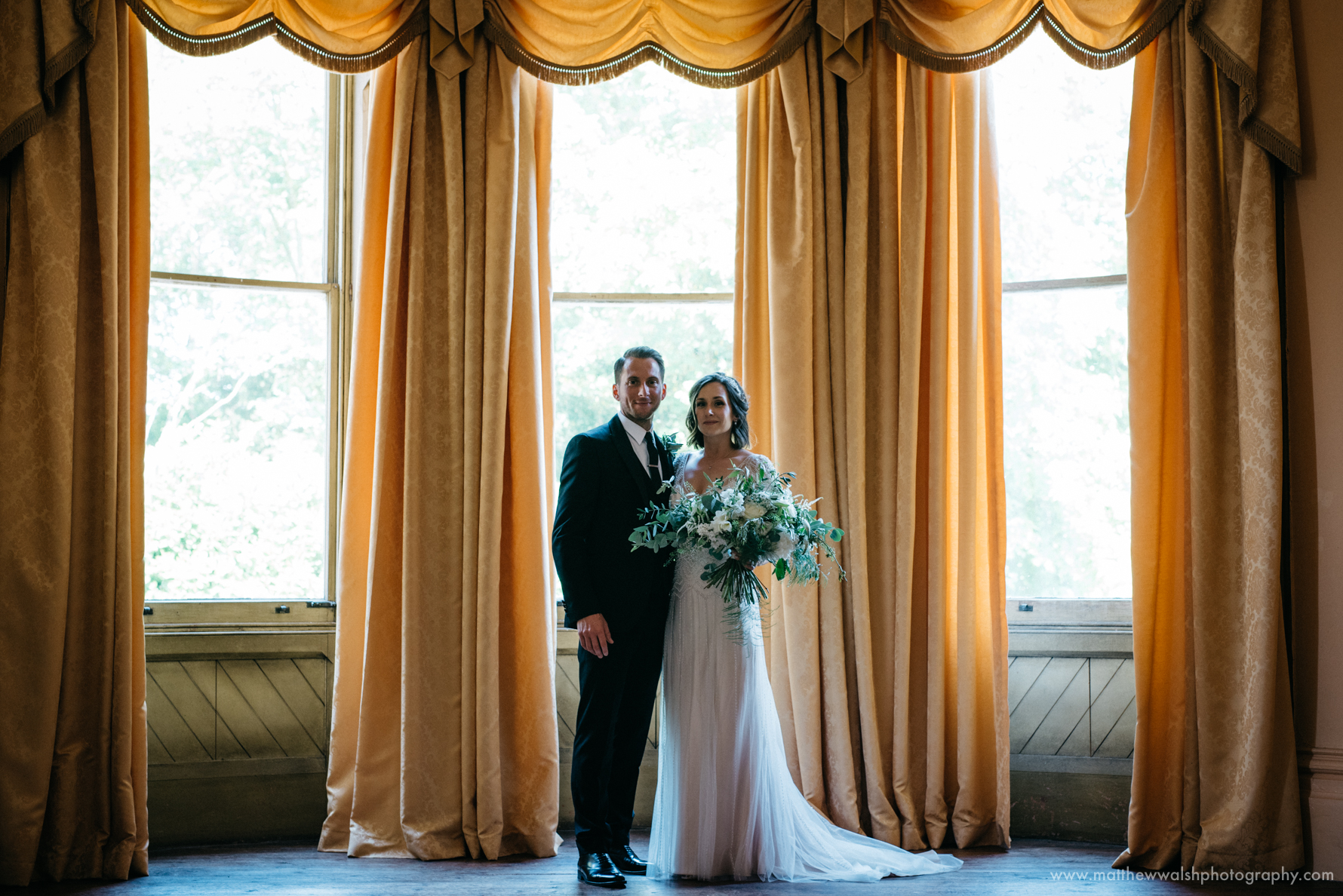 Bride and groom pose for a photograph in front of the big windows