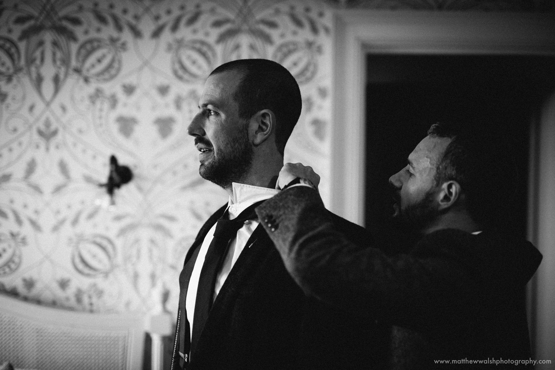 The groom assisting one of the ushers with his collar.