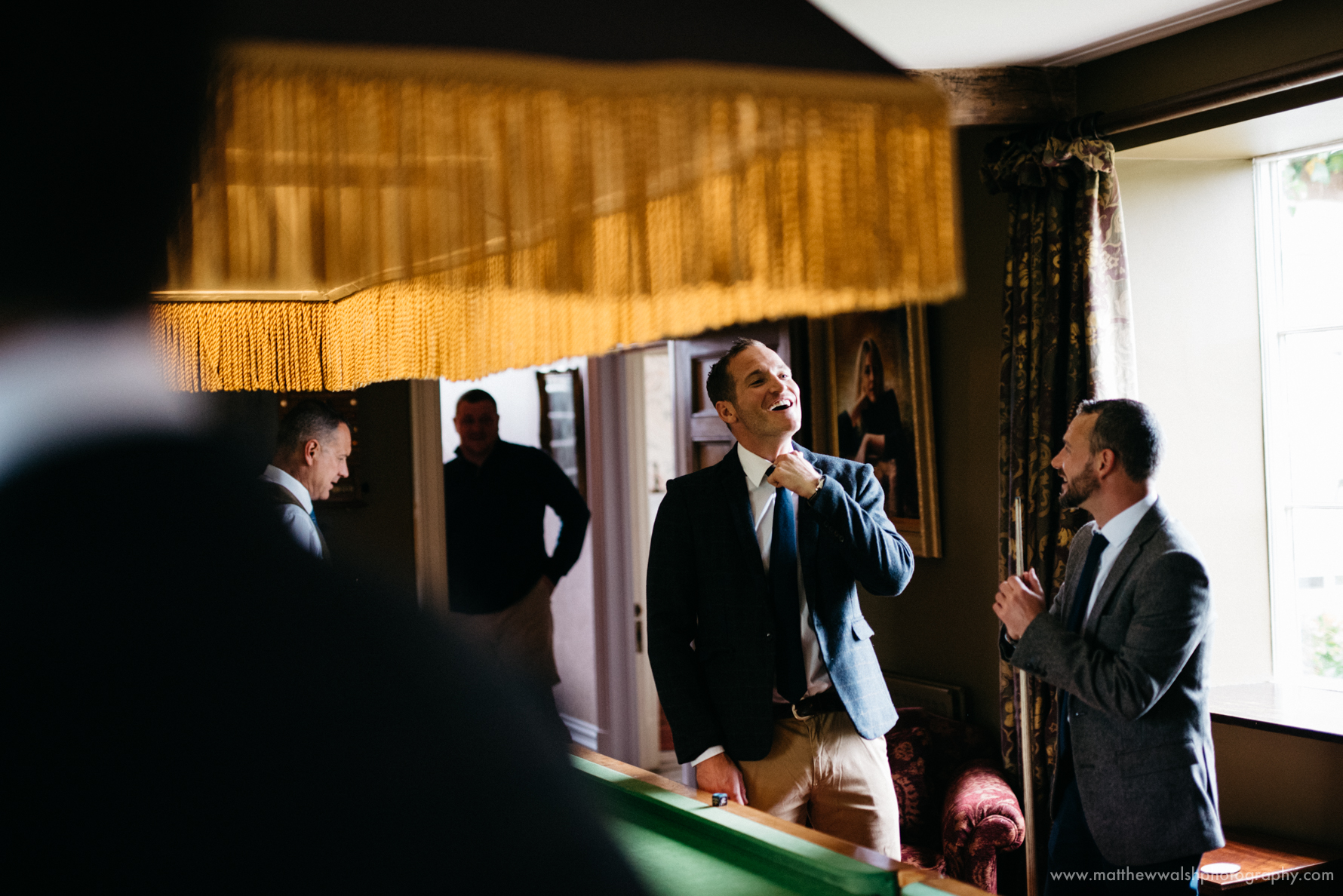 The groom and groomsmen calm the pre ceremony nerves in the billiards room