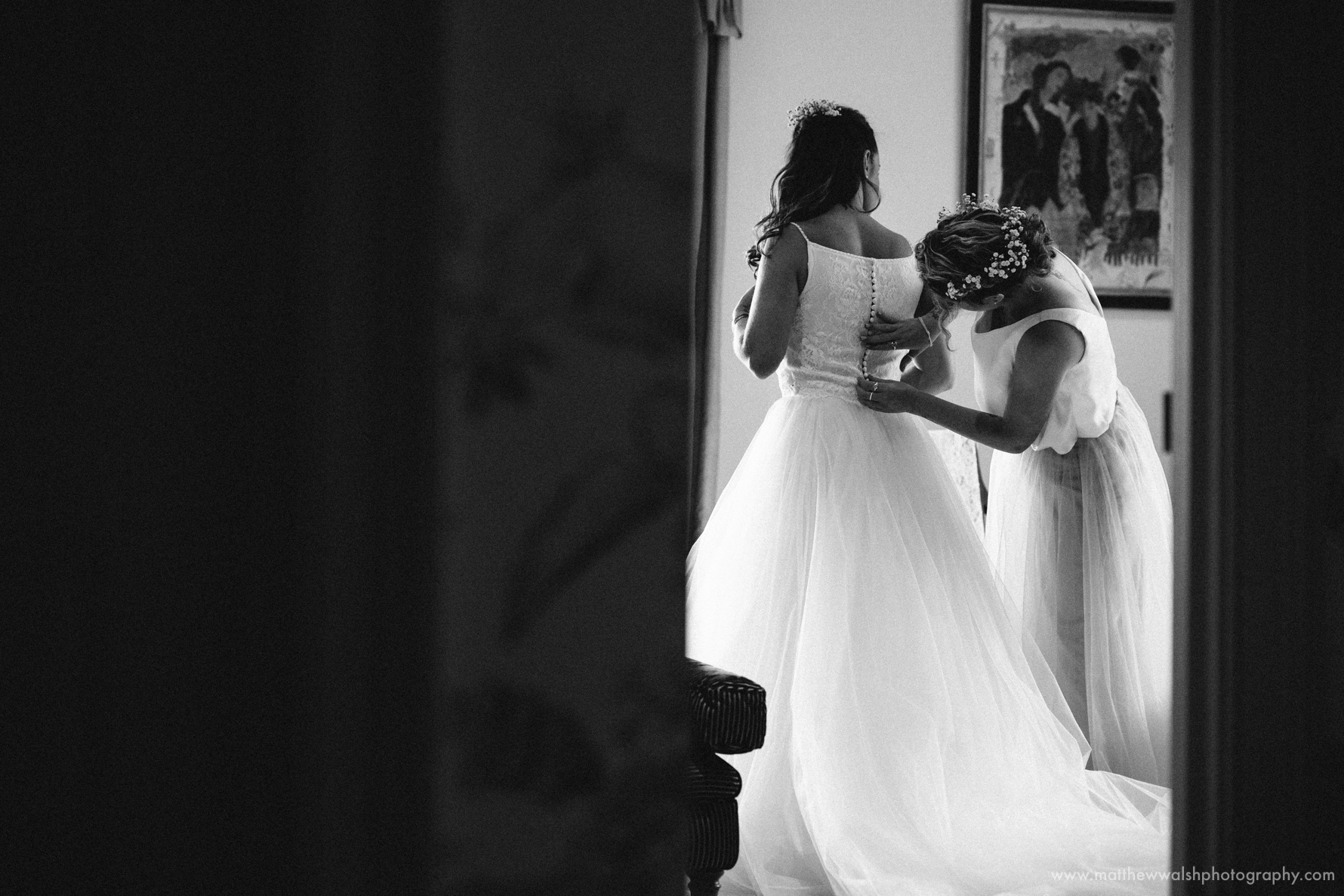 Bridesmaid helping the bride put her wedding dress on