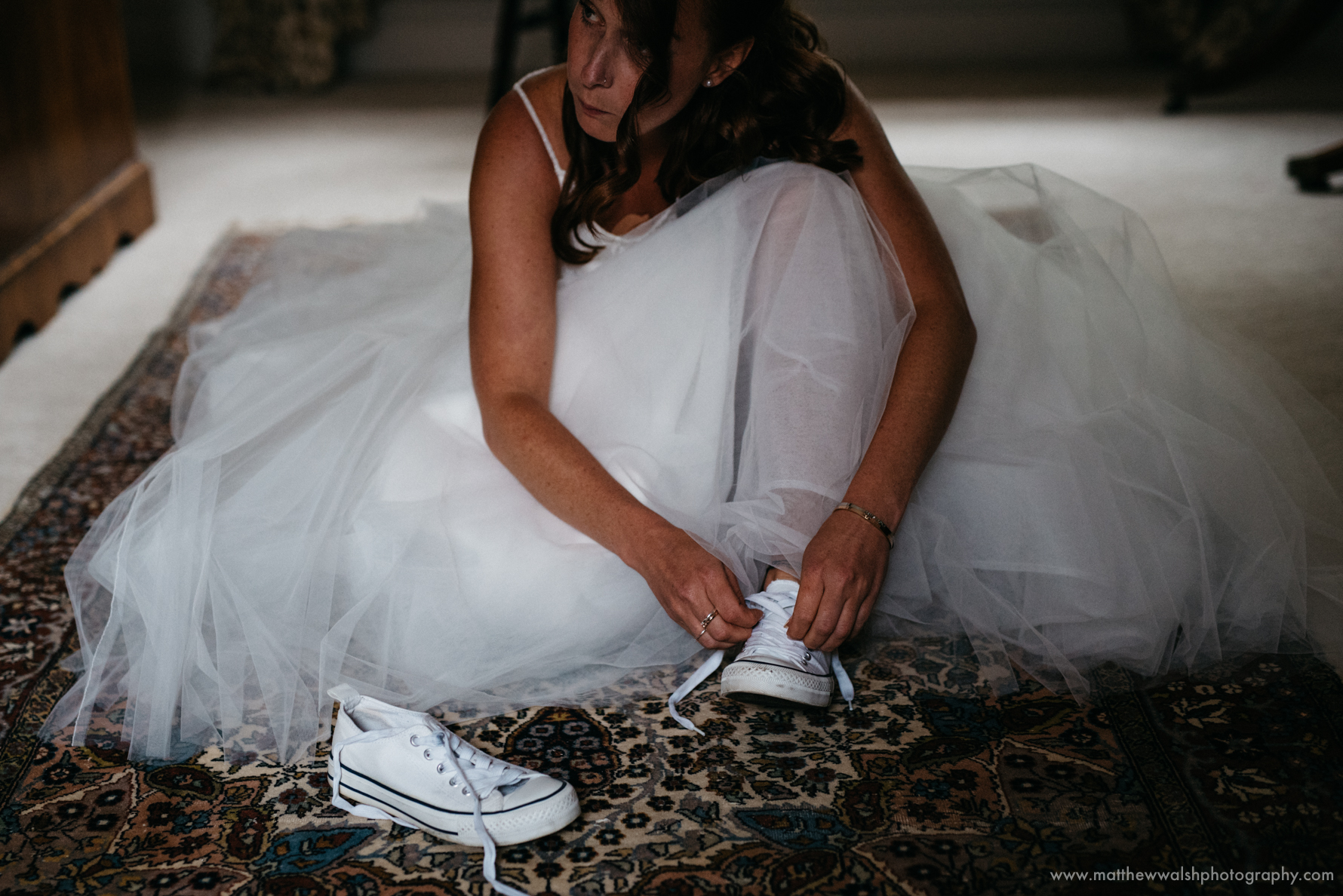 The bride creating a personal touch by ignoring tradition and wearing converse under her dress