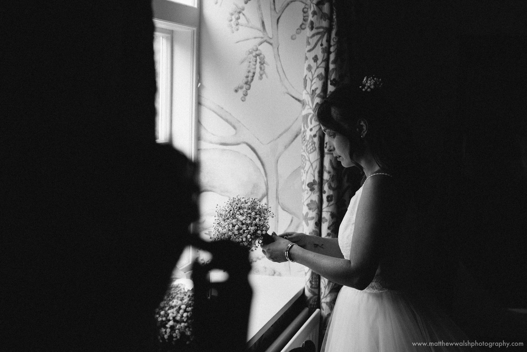 Bride standing by the window lit by fantastic natural light