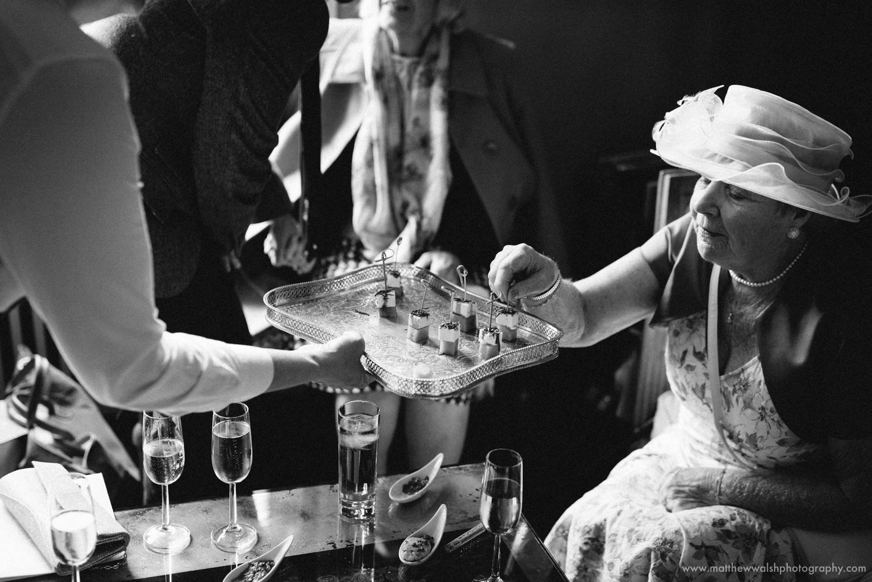 A guest carefully picks a canapé, beautifully captured in black and white