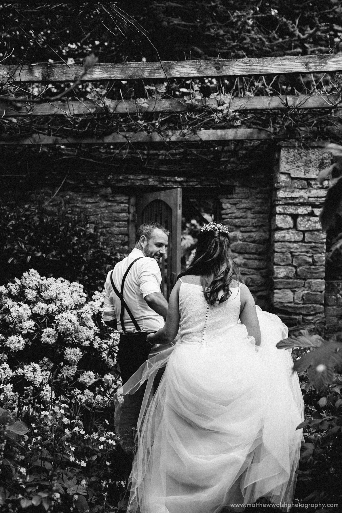 The groom leading the bride through the gardens at Dewsall court, Hereford, Herefordshire