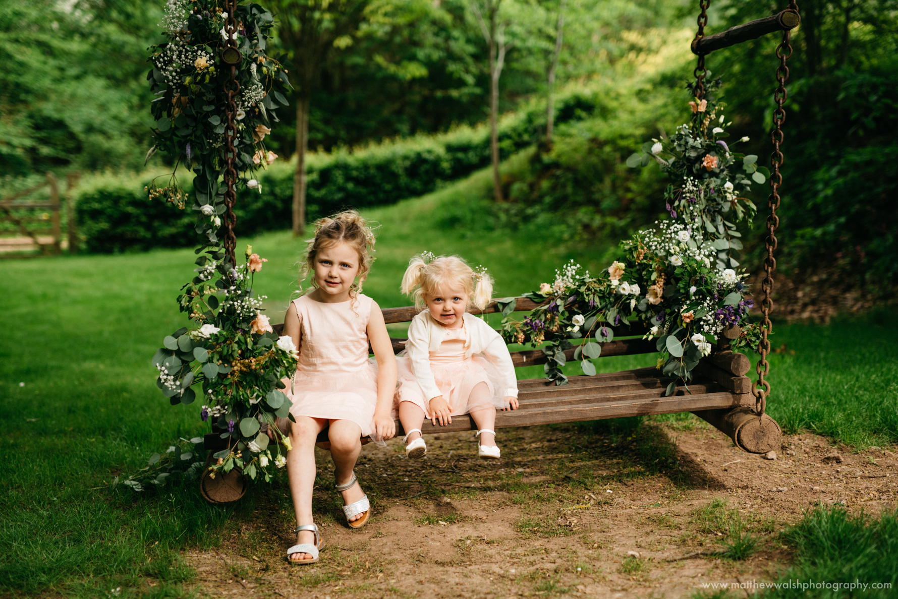 Little flower girls having fun on a swing, as a beautiful early evening light sets in