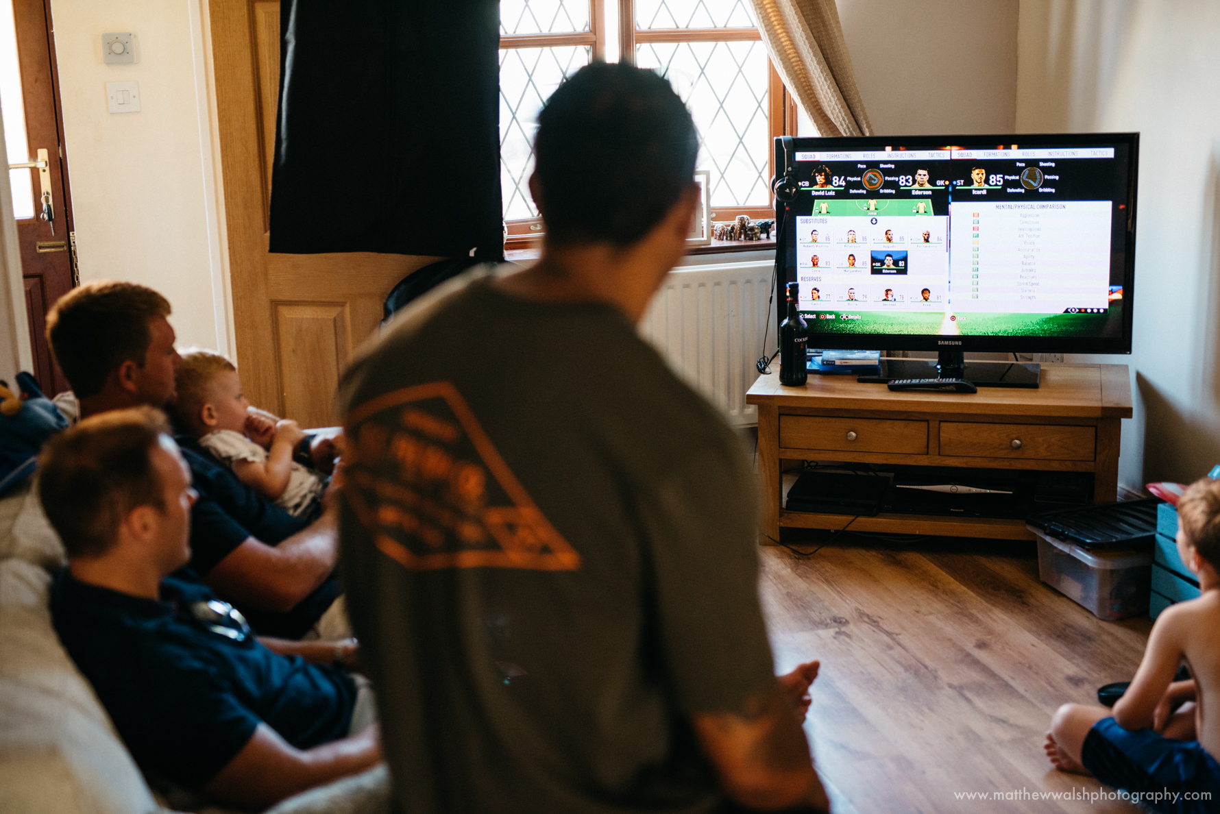 The groomsmen preparing by playing a video game