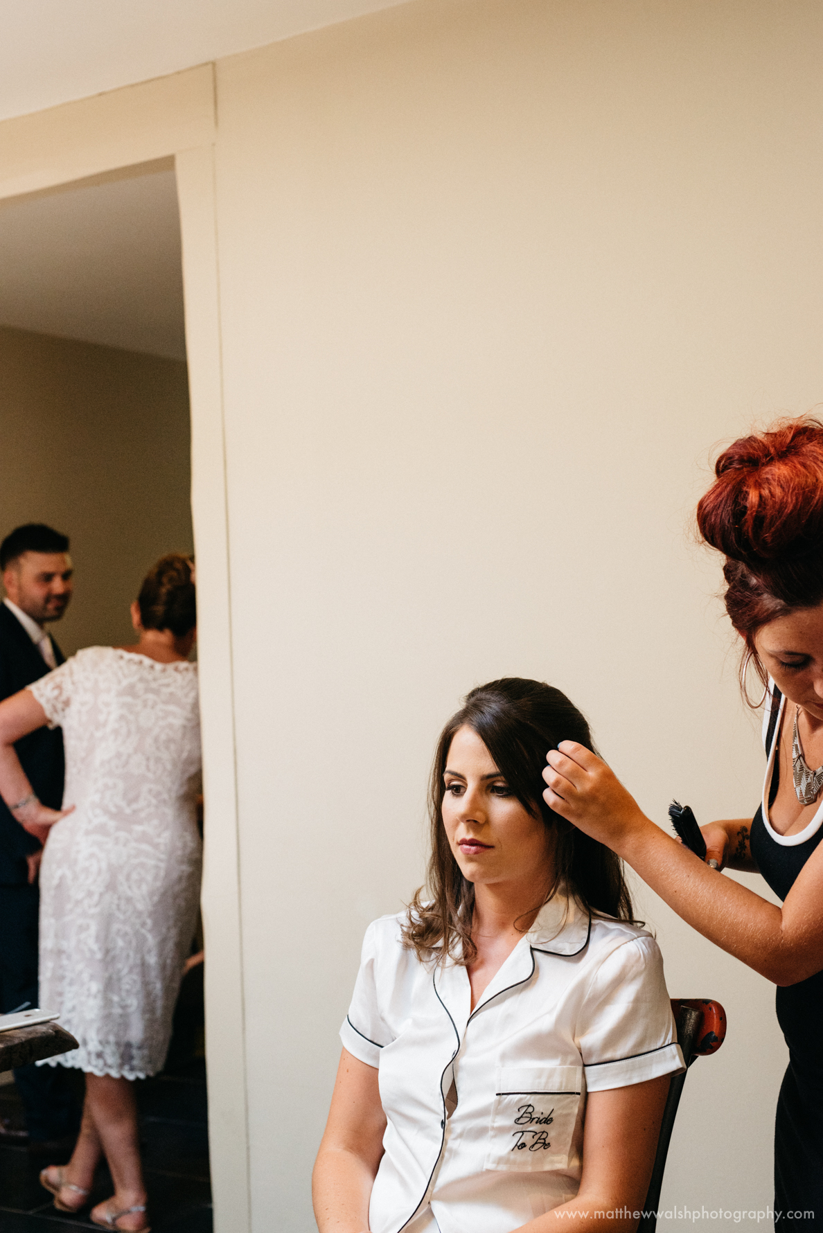 A relaxed photograph of the bride having her hair done