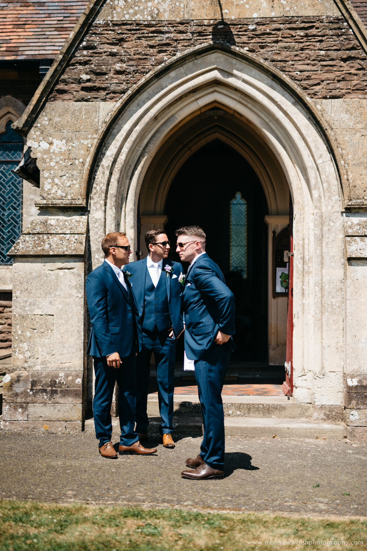 The ushers standing outside the church in the sun waiting for the bridal party