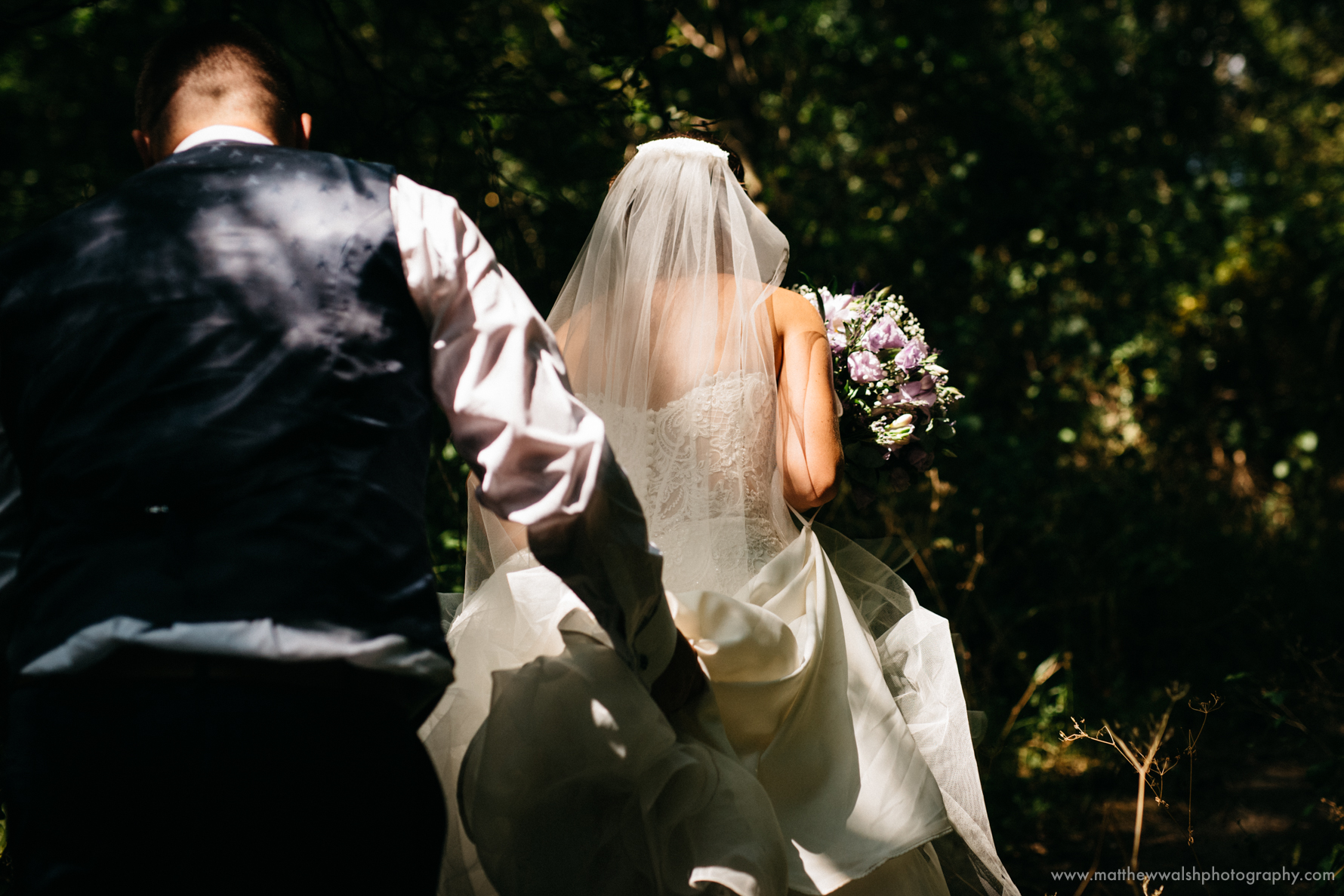 Beautiful natural dappled light falling on the back of there brides dress