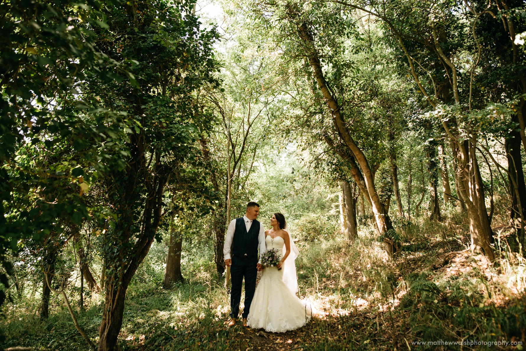 Touching moment as the new husband and wife stand under the artistic dappled light of the trees